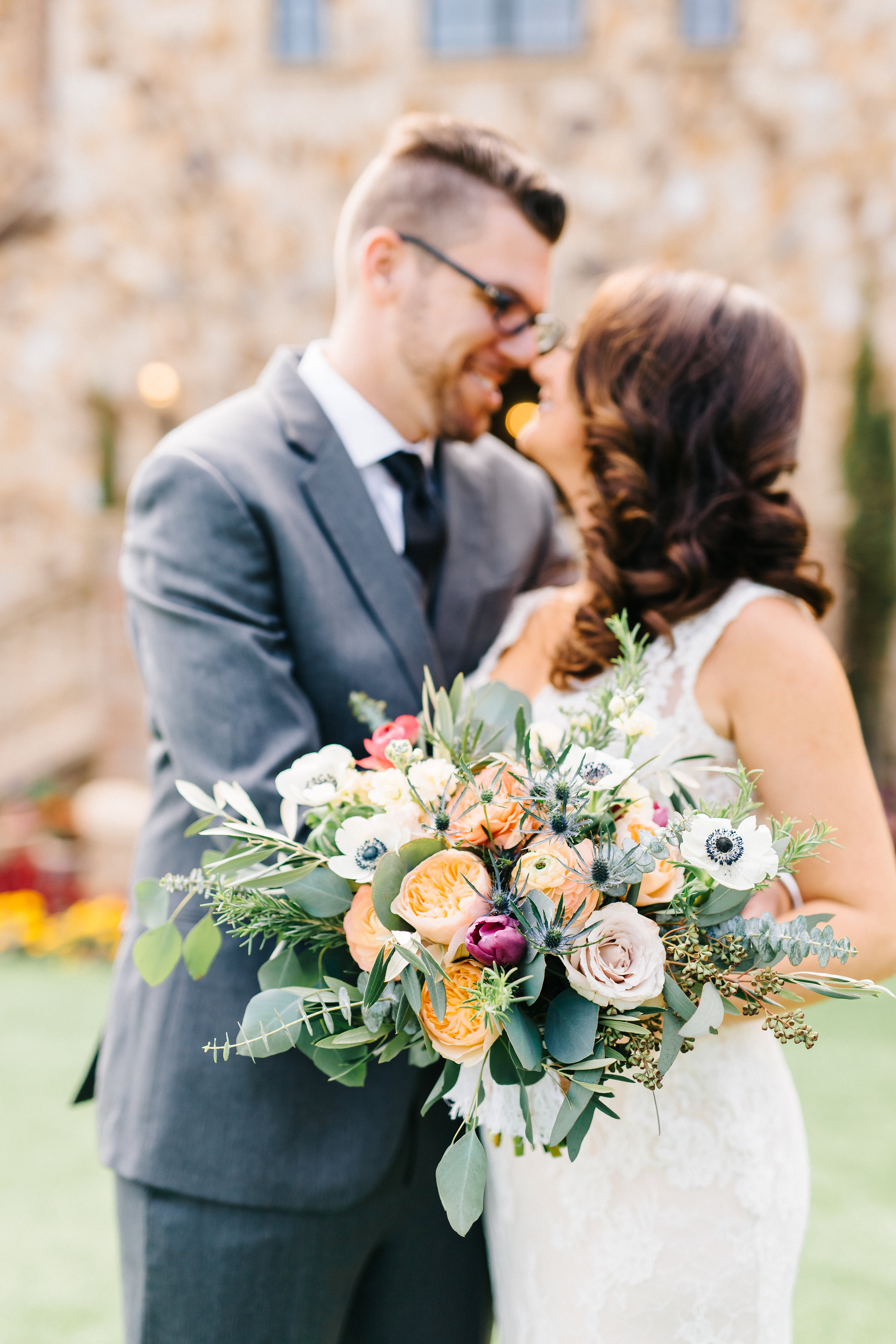 Bridal bouquet with anemones, garden roses, eucalyptus and olive leaf  Orlando Wedding Planner Blue Ribbon Weddings  Orlando Wedding Photographer Emma Shourds Photography  Wedding Ceremony at Bell Tower at Bella Collina  Wedding Reception in Atrium at Bella Collina