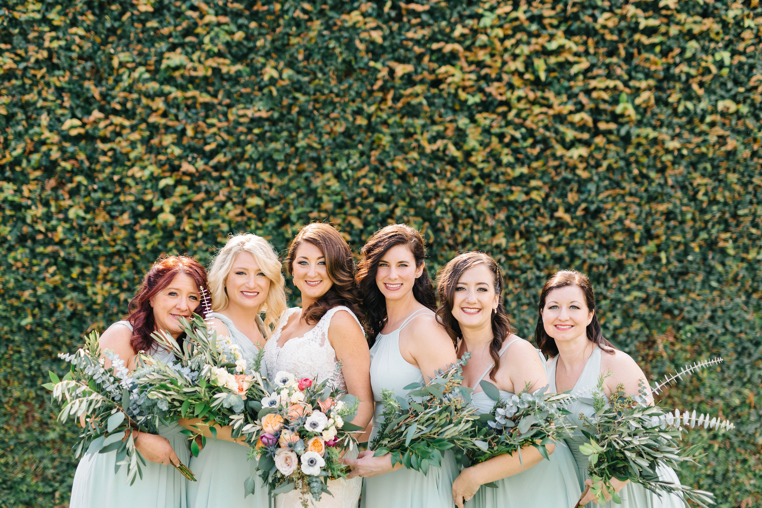 Bridal bouquet with anemones, garden roses, eucalyptus and olive leaf  Bridesmaids in dusty green with eucalyptus and olive leaf bouquets  Orlando Wedding Planner Blue Ribbon Weddings  Orlando Wedding Photographer Emma Shourds Photography  Wedding Ceremony at Bell Tower at Bella Collina  Wedding Reception in Atrium at Bella Collina