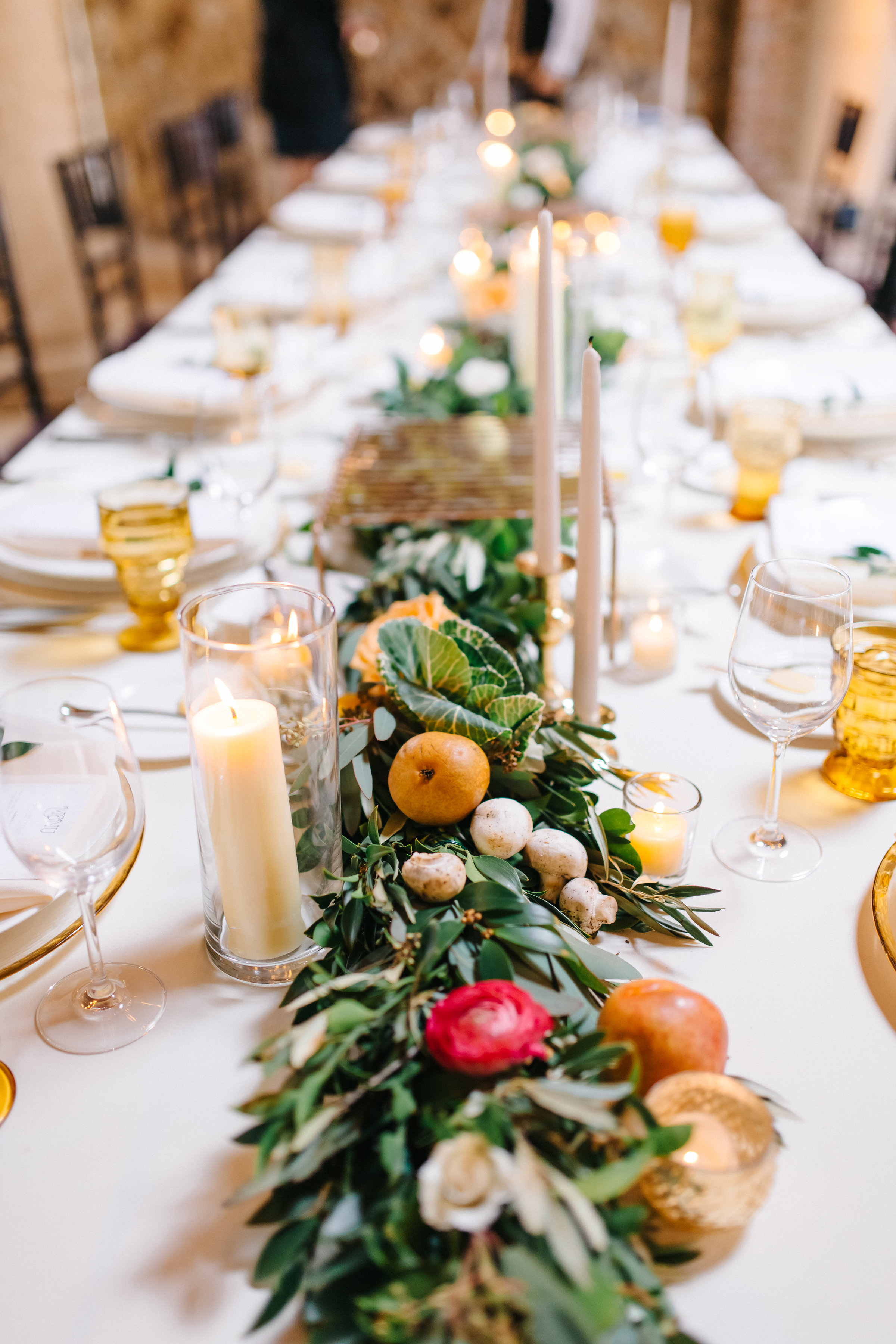 Alfresco tuscan wooden farm table tablescape with vegetables and fruit nestled in greenery  Orlando Wedding Planner Blue Ribbon Weddings  Orlando Wedding Photographer Emma Shourds Photography  Wedding Ceremony at Bell Tower at Bella Collina  Wedding Reception in Atrium at Bella Collina