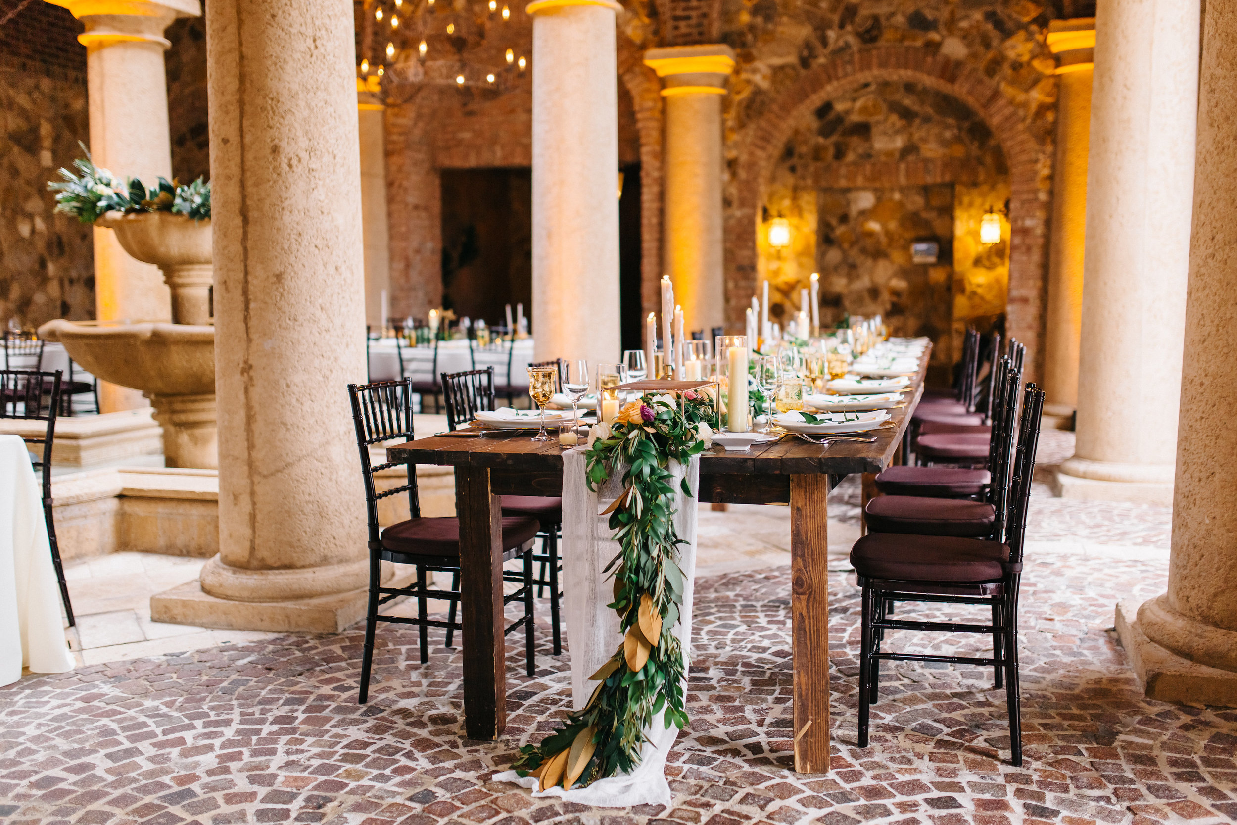 Candlelit tuscan inspired wedding reception with olive leaf and magnolia greenery  Tuscan inspired alfresco wedding reception with olive leaf and magnolia greenery  Orlando Wedding Planner Blue Ribbon Weddings  Orlando Wedding Photographer Emma Shourds Photography  Wedding Ceremony at Bell Tower at Bella Collina  Wedding Reception in Atrium at Bella Collina