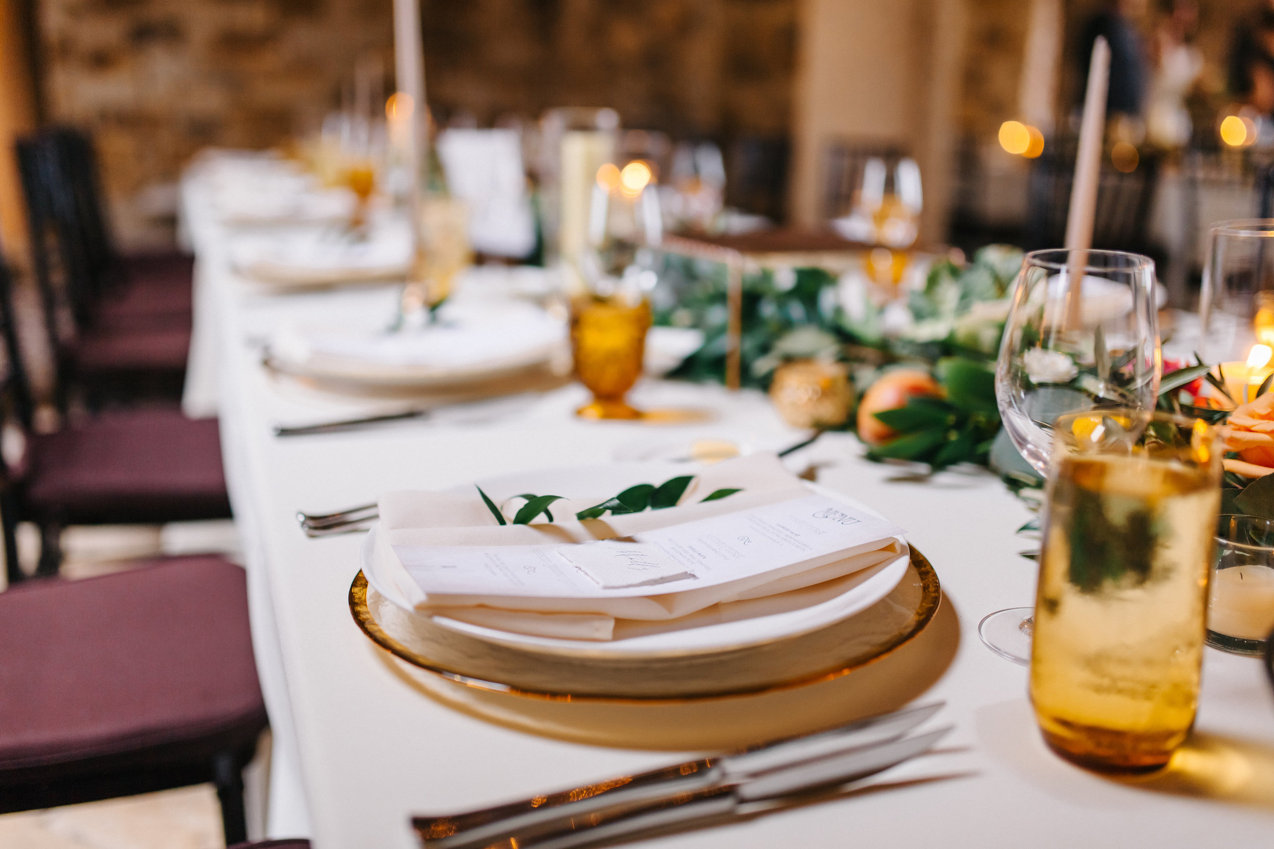 Candlelit tuscan inspired wedding reception with olive leaf and magnolia greenery and colored glassware  Orlando Wedding Planner Blue Ribbon Weddings  Orlando Wedding Photographer Emma Shourds Photography  Wedding Ceremony at Bell Tower at Bella Collina  Wedding Reception in Atrium at Bella Collina