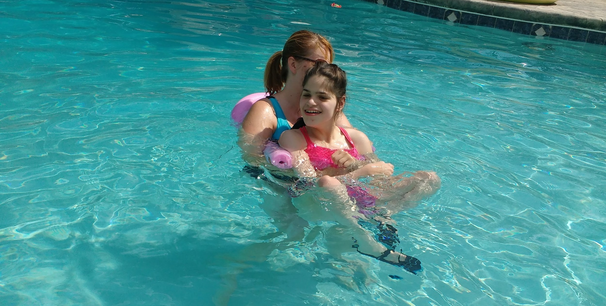 Sofia and her PT Christie, enjoying therapy in the pool.