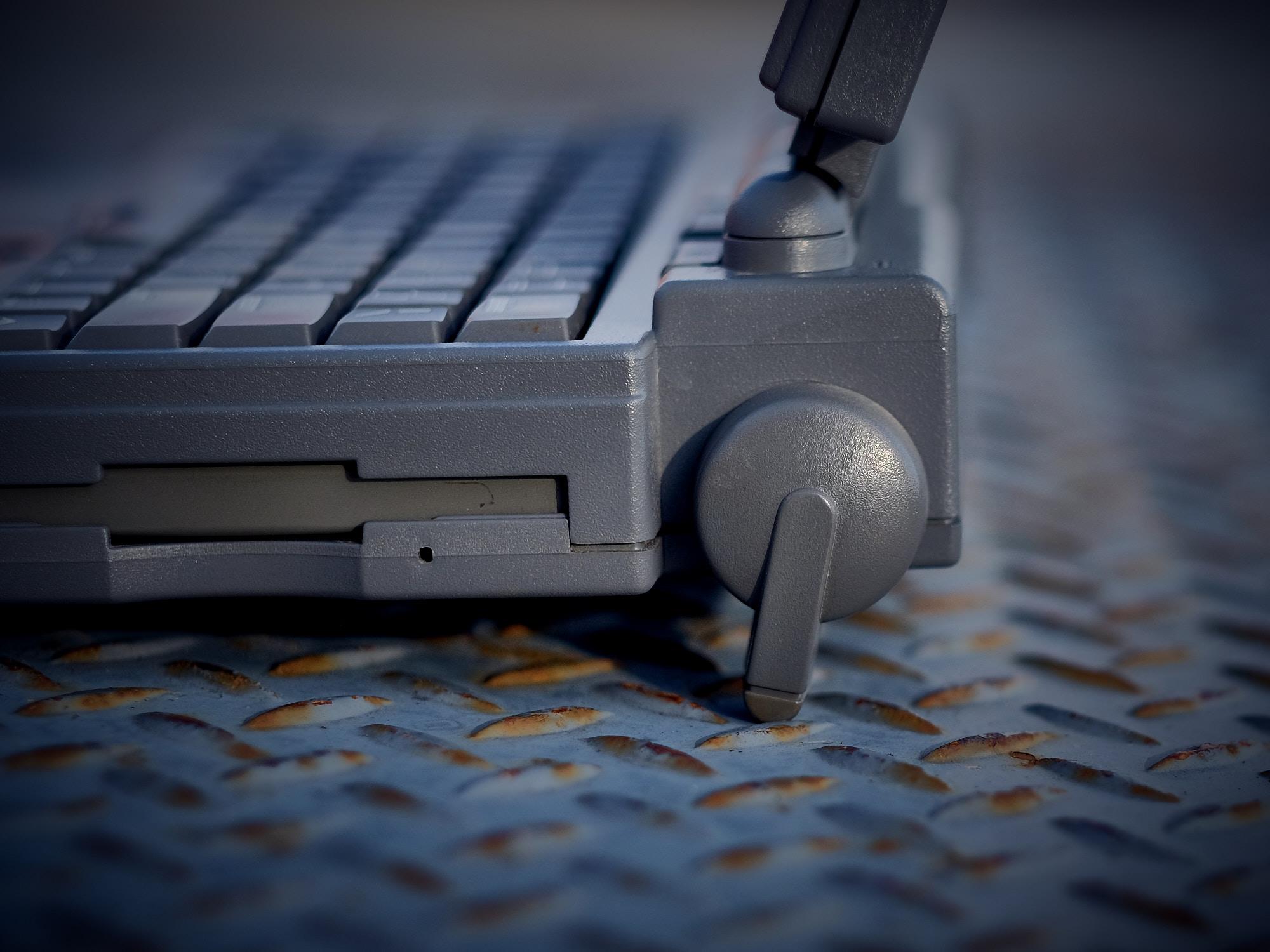 Feet raising the laptop. Floppy drive on left.