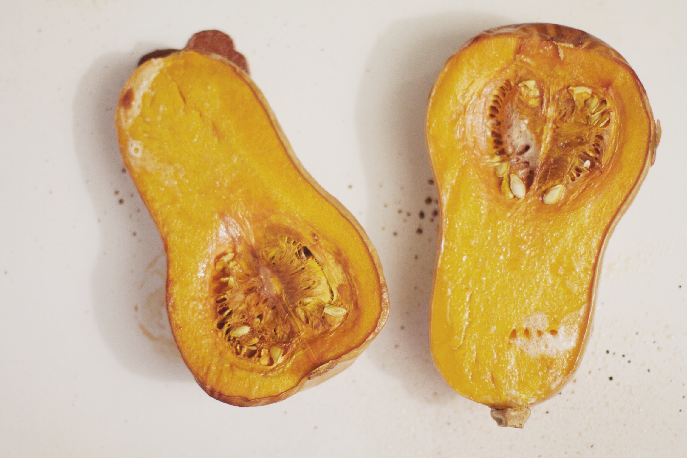 Preheat oven to 350 degrees fahrenheit, slice butternut squash in half, drizzle slightly with olive oil and once oven is heated place squash cut side down. Bake at 350 degrees F for about 60 minutes. Squash should be fork tender and the skin should peel right off.