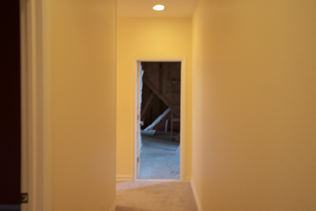 Sorry for the blur. This is from just past the middle of our upstairs hall, looking toward the east. On the left is a door into a bedroom, which will be a casualty of our renovation. We'll be talking out about the eastern half of the room to open up that end of the hallway. The remaining half will be the new linen and storage closet. We'll also add a skylight. Directly ahead is the open door into the attic space over the east end of the house. If you turn the corner and go left, instead of into the attic, there is a linen closet—another casualty— right next to the attic doorway. Then, after the linen closet, there is the back stairway that leads down into the laundry room.
