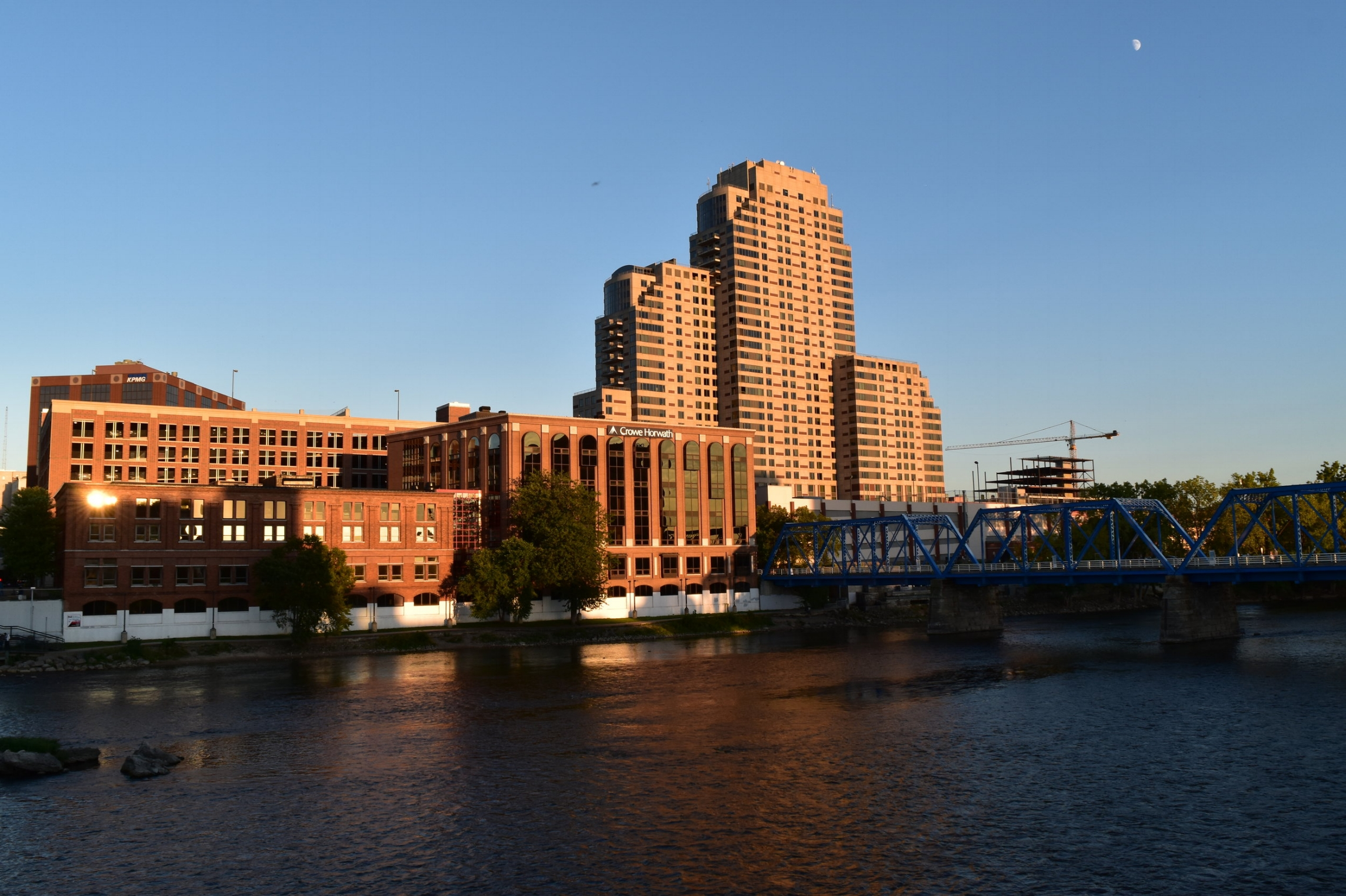 Dominion Systems has an office in Grand Rapids, MI showing blue bridge with big brick buildings in city.