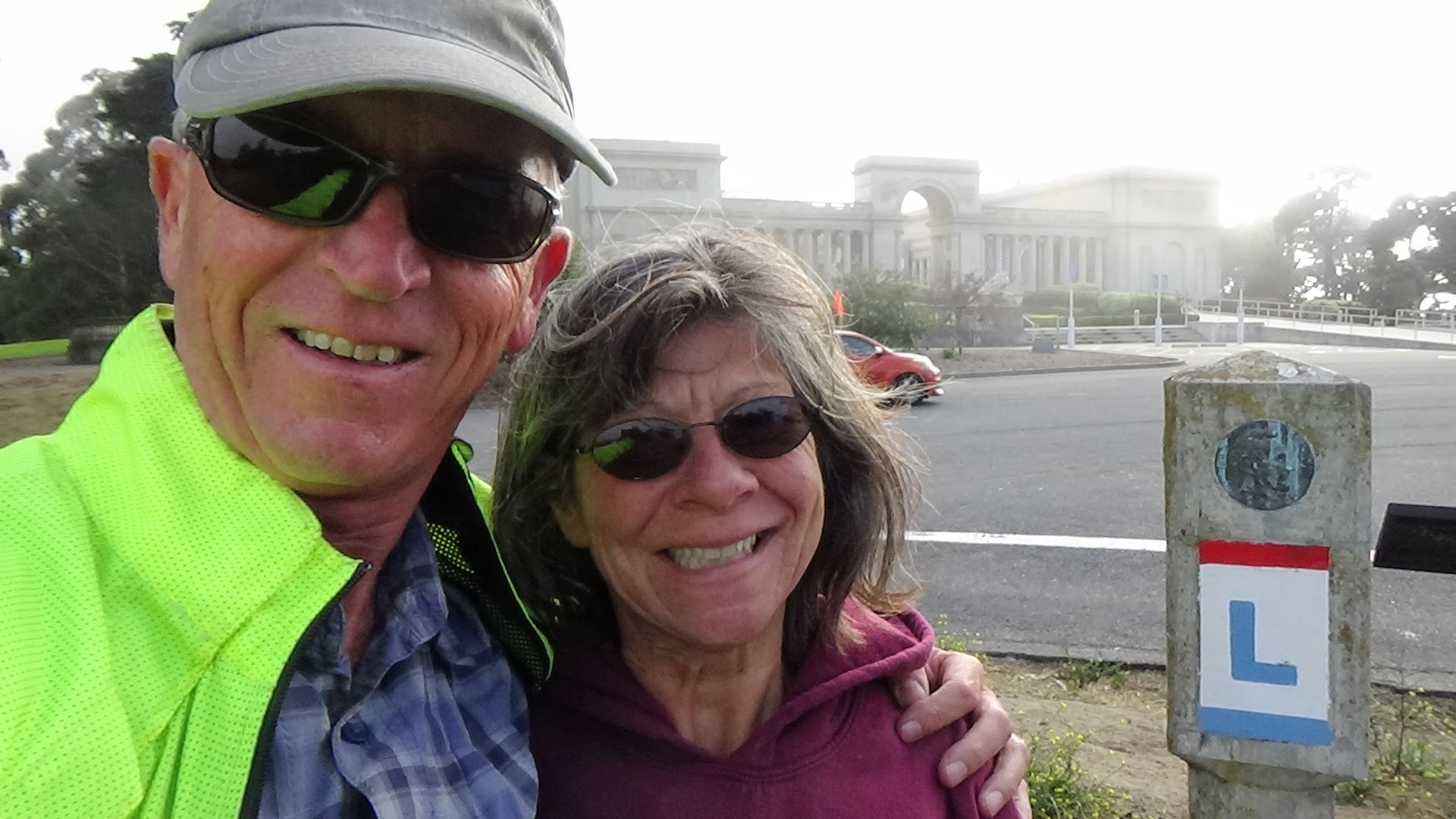 Trey and Monica at The Palace of the Legion of Honor standing next to the  Lincoln Highway Terminus marker.