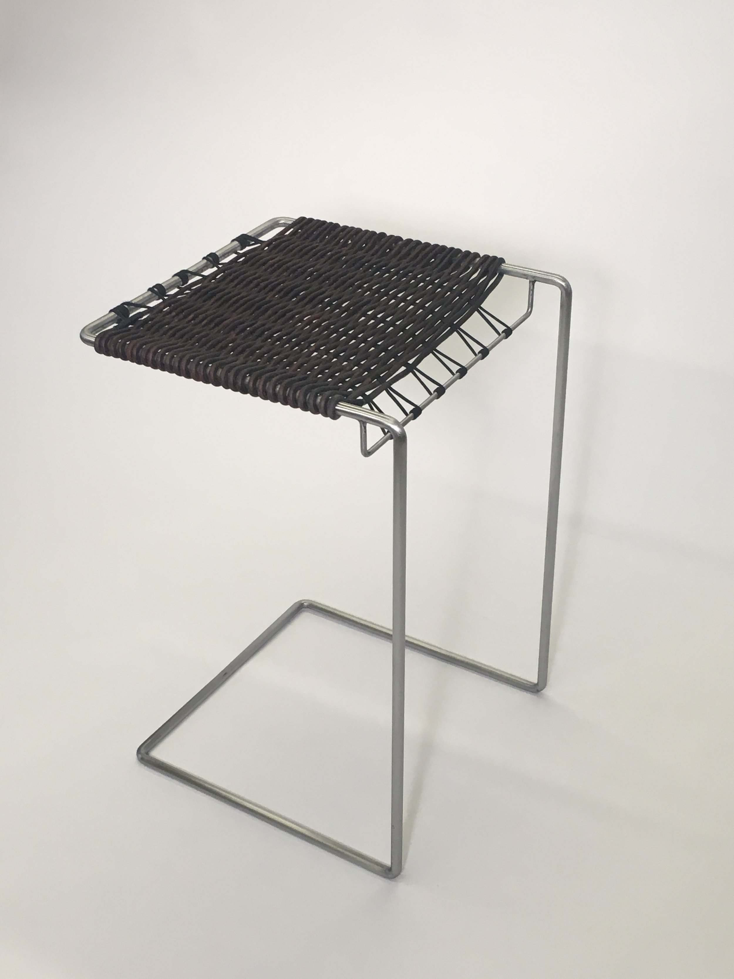 Bent steel and woven leather table
