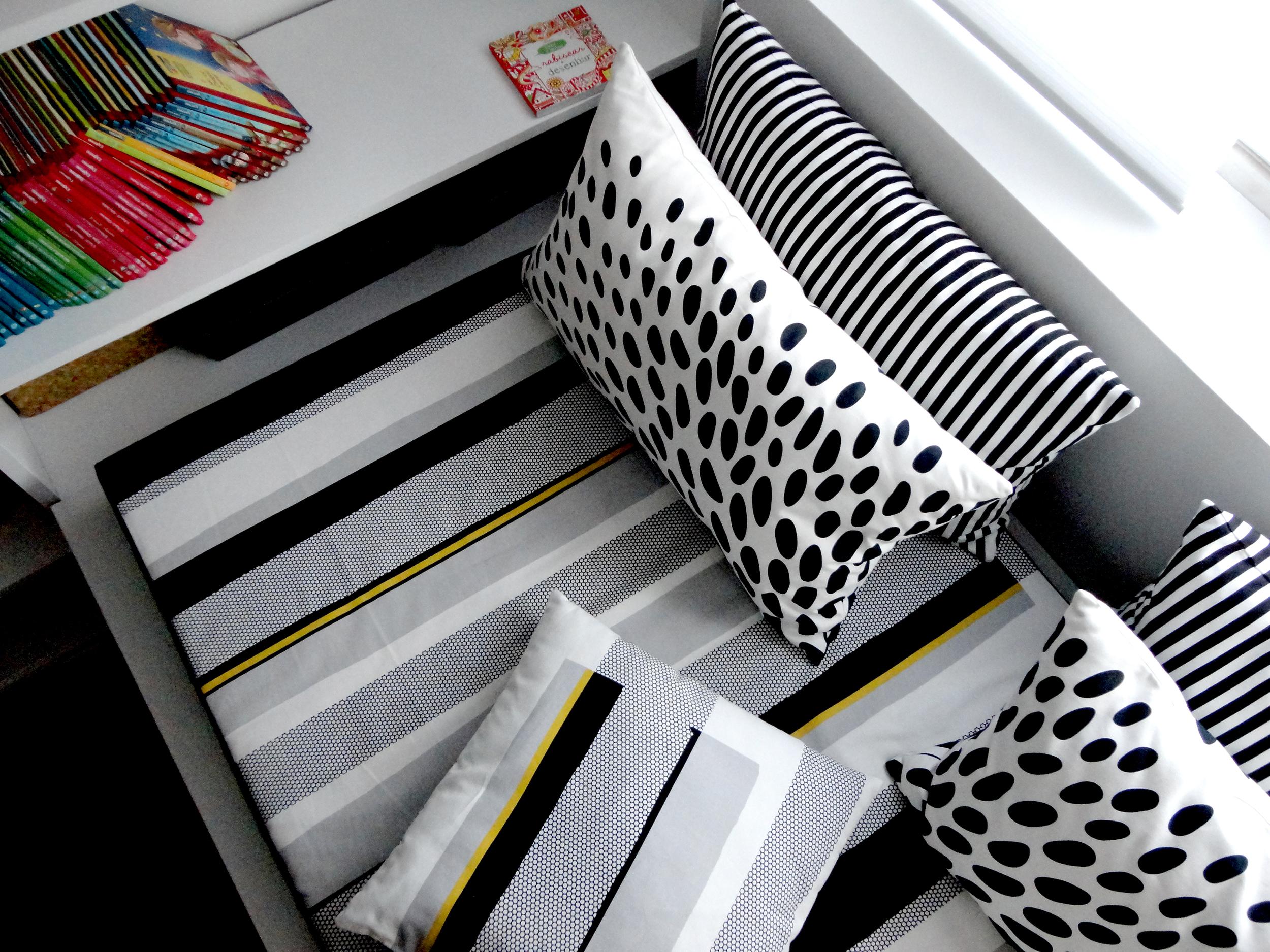 """A """"day bed"""" junto à janela cheia de almofadas para o conforto necessário."""