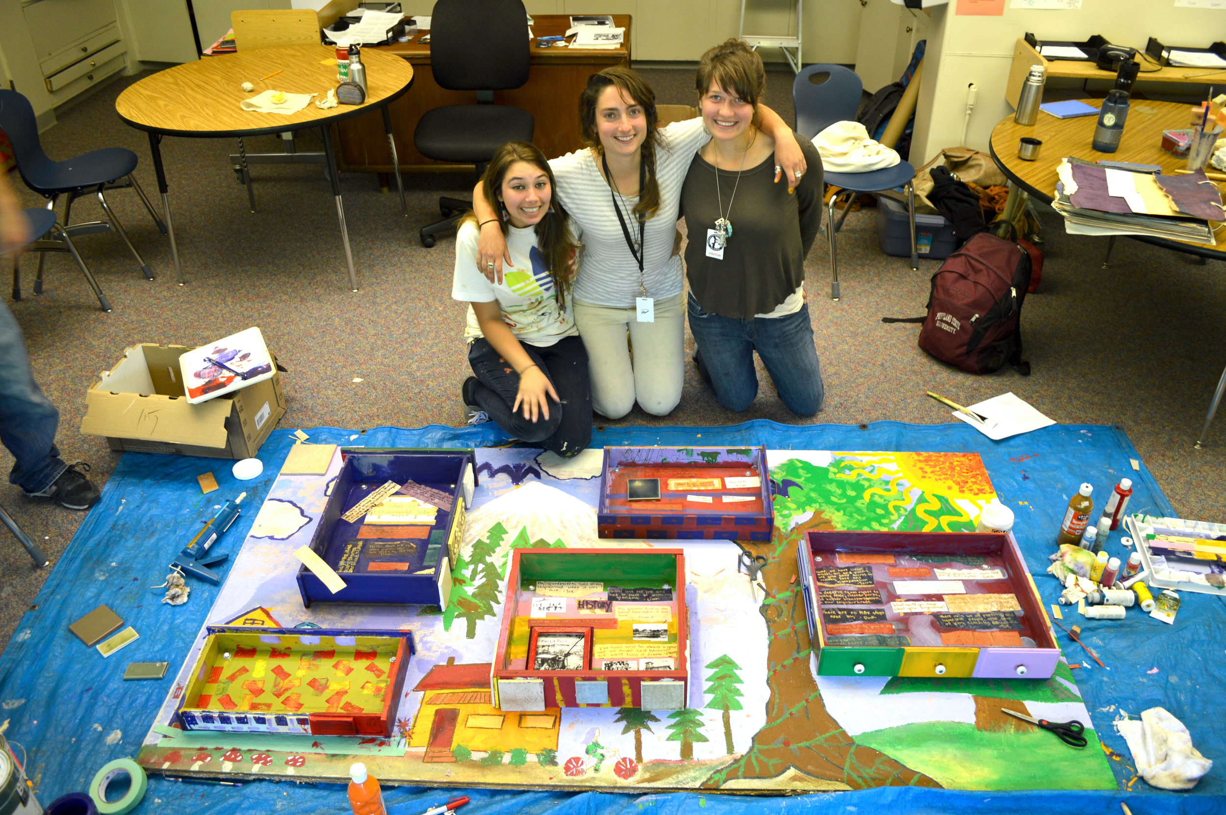 Claudia, Laura and Katie with their environmental justice mural made with high school students
