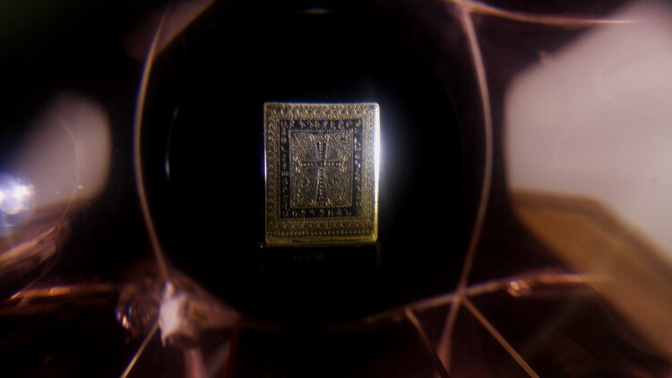 Армянский хачкар изображён на янтарной пластине размером 8х6 мм. По периметру выгравирован армянский алфавит. Автор микроминиатюры – Эдуард Тер-Казарян