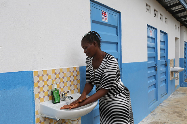 A woman washes her hands at a newly constructed WASH facility at the Konta Line Community Health Centre. Just last year there were no handwashing stations at the centre.  © UNICEF Sierra Leone/2017/Mason