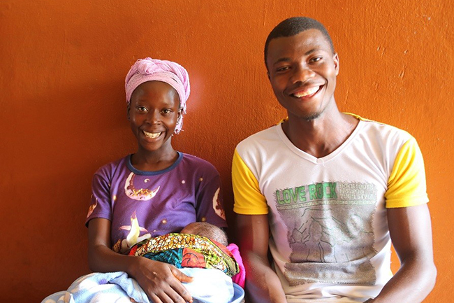 """Isatu Conteh sits with her husband and baby. She has given birth at the Konta Line Community Health Centre both before and after the renovations. """"This time I didn't have to take a tough walk to the stream to bathe and wash my baby's clothes,"""" she says. © UNICEF Sierra Leone/2017/Mason"""