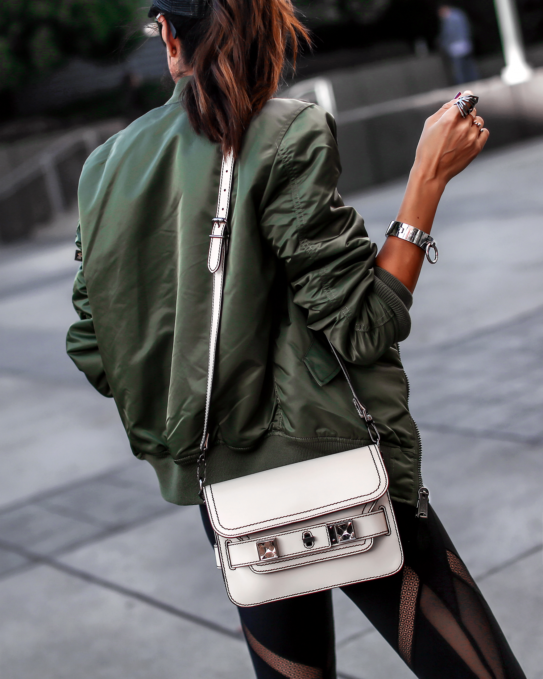 Brunette Woman Bomber Jacket and White Purse