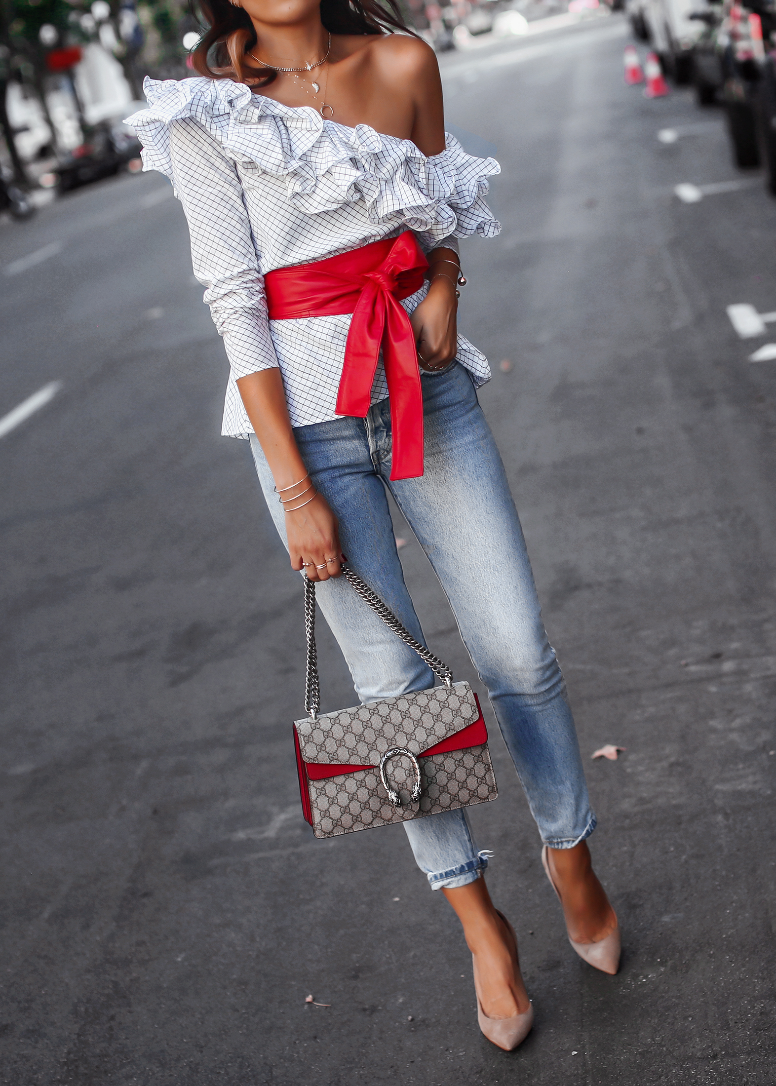 Brunette Woman Walking in Levis and One Shoulder Top