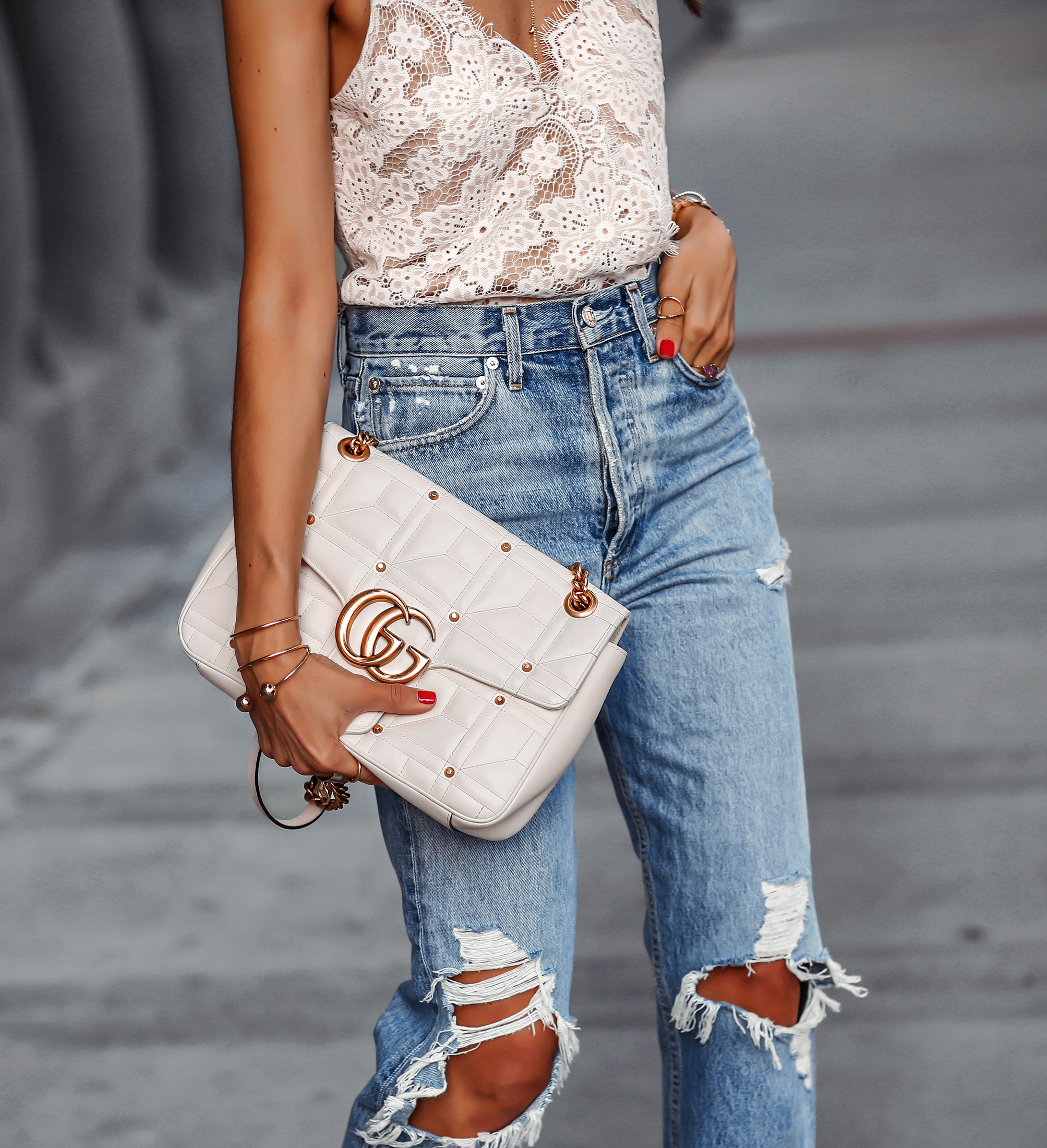 Details Shot of Woman Ripped jeans White Gucci Marmont Bag