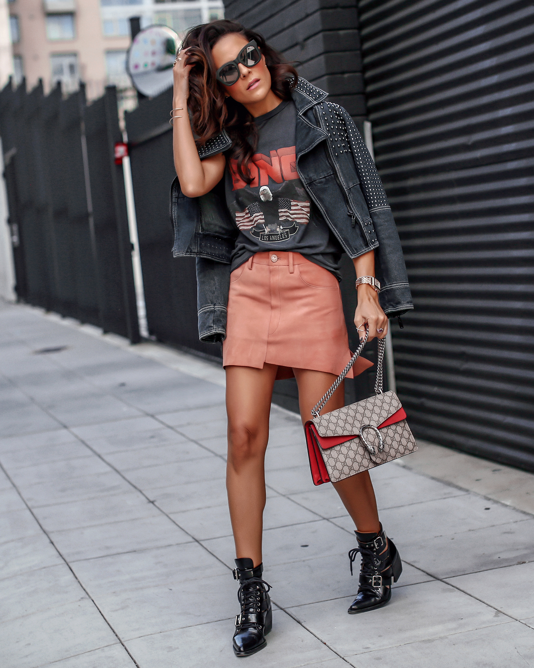 BRunette Woman in Peach Suede Skirt Graphic Tee Chloe Boots