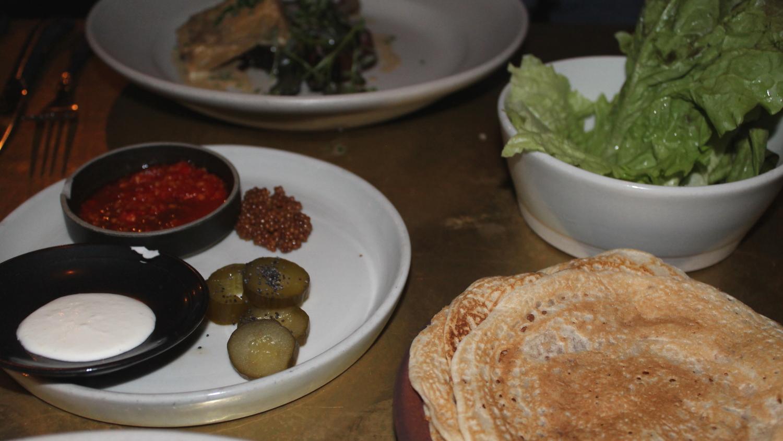 Lettuce, sourdough flatbread, and an assortment of sauces.