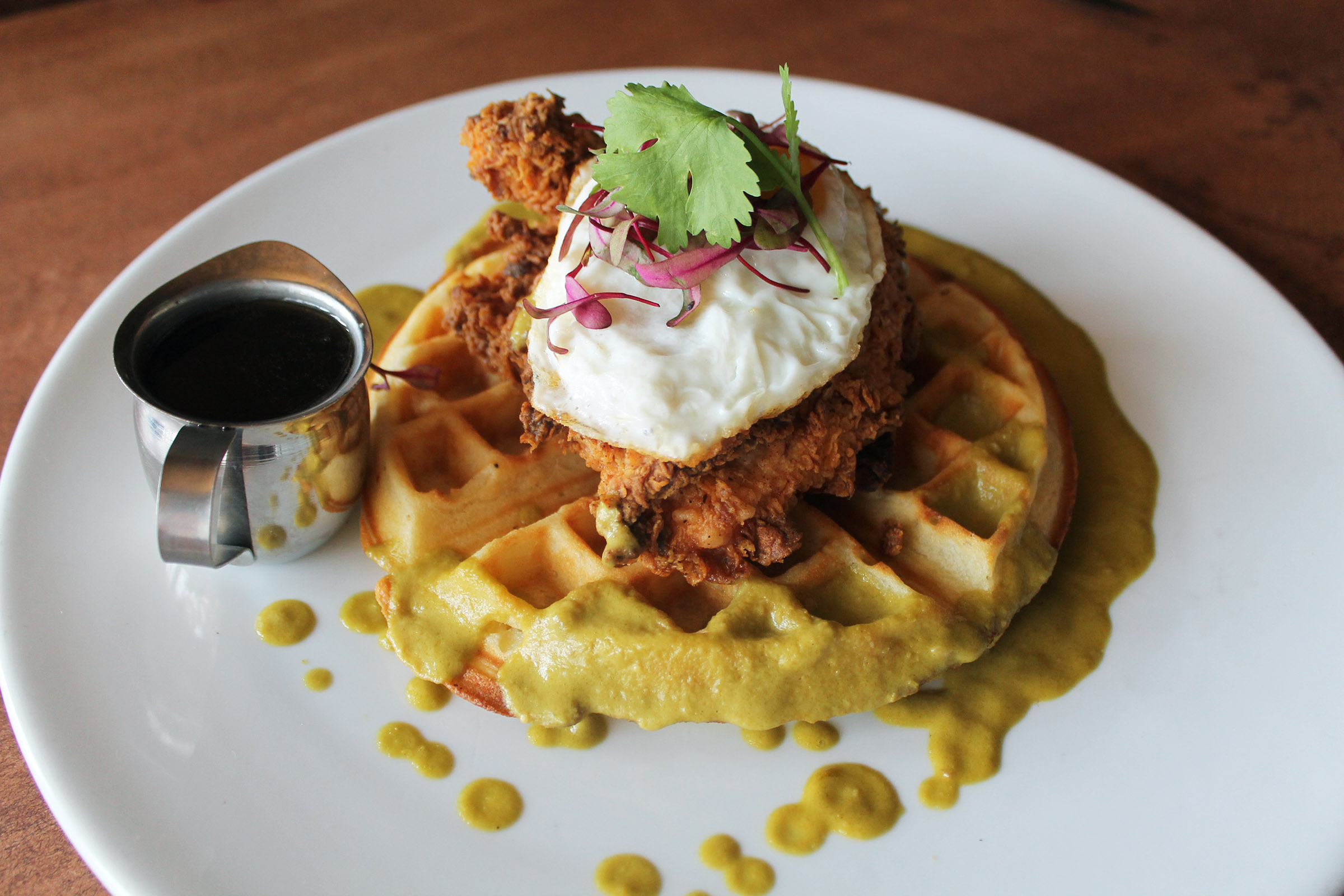 Chicken and Waffles: Fried Chicken Breast, Belgian Waffle, Fried Egg, Poblano Sauce, Maple Syrup
