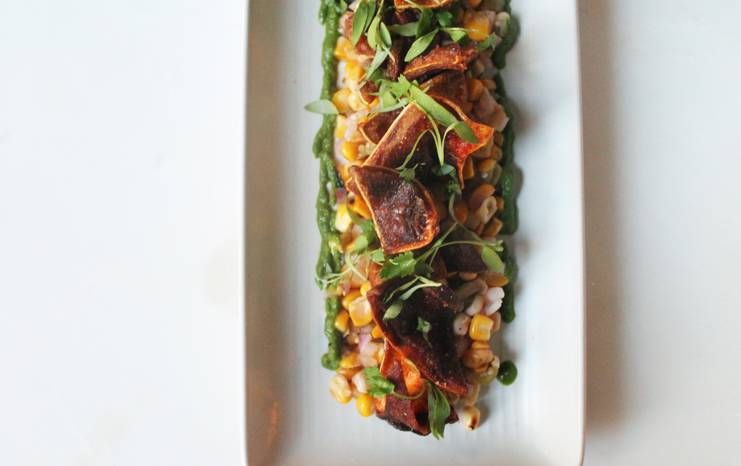 Summer corn and tomatillo salad with crispy pig ears