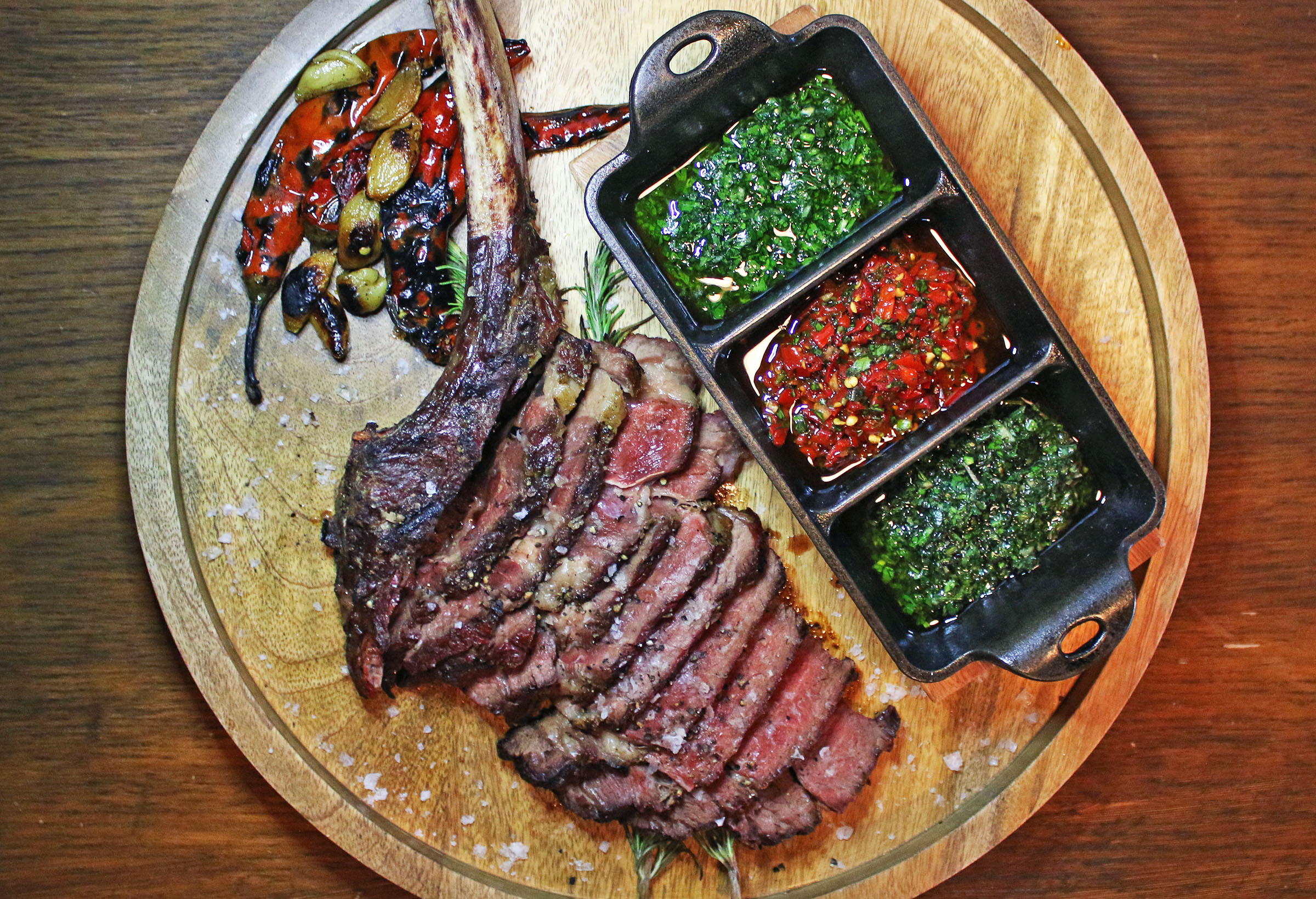 28 oz dry aged Tomahawk aged 28 days, with a parsley salsa verde, Italian chimichurri and a Calabrian chile salsa