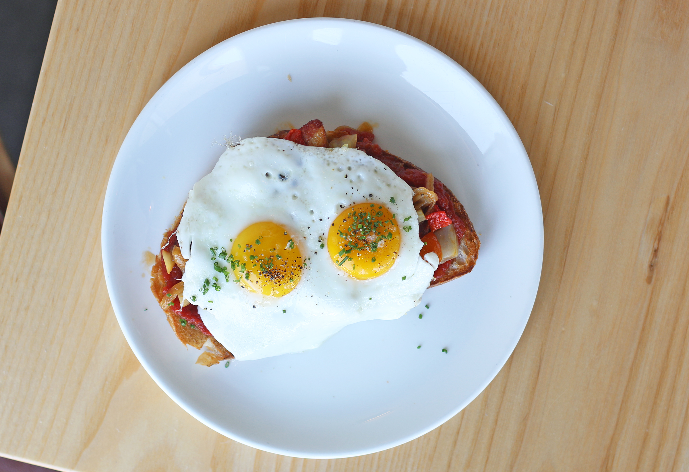 PORK BELLY TOAST: sunny side up eggs, tomato marmalade, piquillo peppers, cherry tomatoes, confit fennel