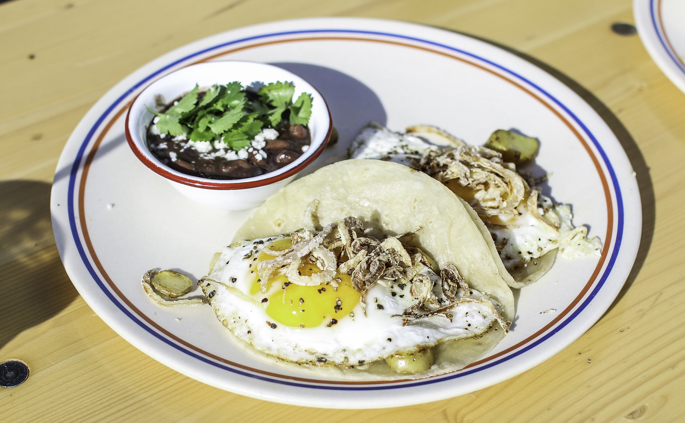 Boardwalk Clasico Tacos: Fried Egg, Fingerling Potatoes, Smashed Avocado, Crispy Shallot served on Housemade Flour Tortillas