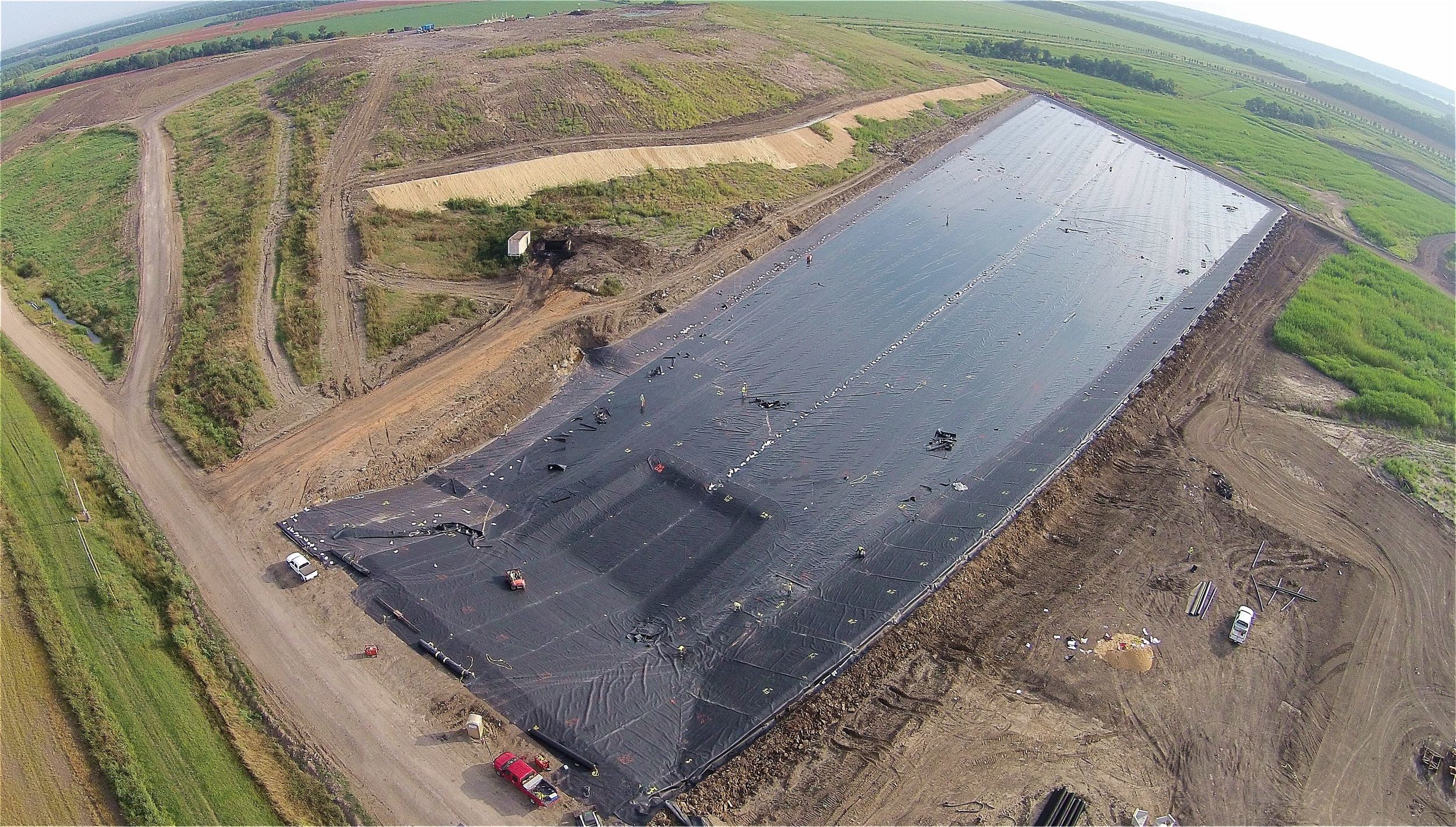 Same site as below (Mississippi Delta), during the HDPE geomembrane liner installation above the compacted clay liner.