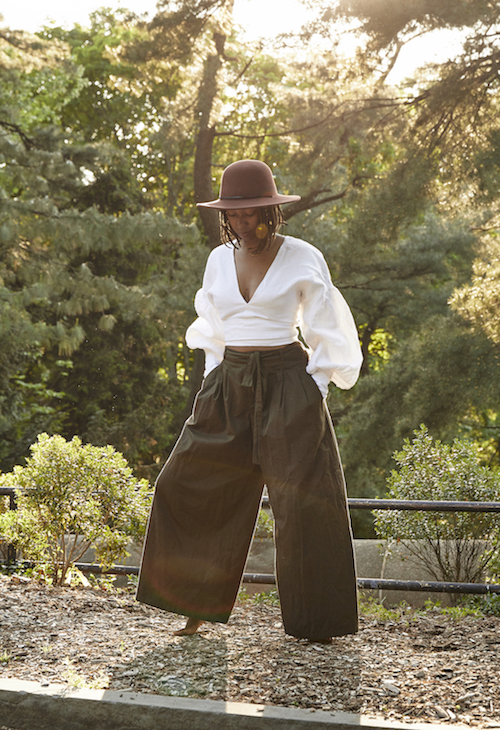 Fall Outfit Inspiration From Sustainable Style Bloggers - Dominique Drakeford in wide-legged green pants with white balloon sleeve top