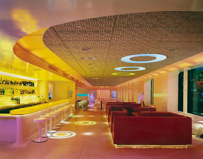 Front bar & lounge - back-lit amber resin counter, lounge seating unit of red urethane foam, acoustic foam tiles for sound-absorbent ceiling, stairs in back with rubberized escalator handrails leading to main dining area