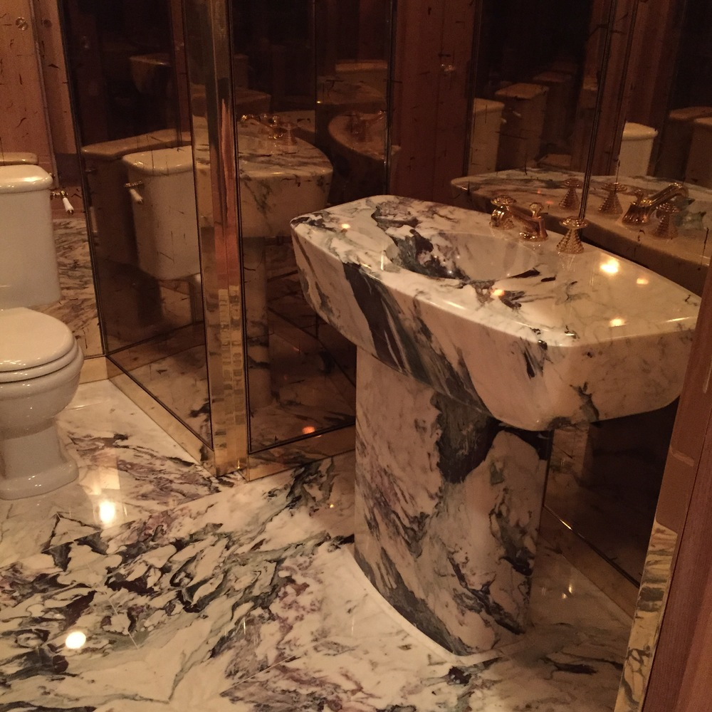 Book-matched Capraia marble floor slabs, carved Capraia marble vanity from the same block, custom water-gilded gold leaf mirrors, bronze trim by Roo Trimble and Brent Trimble