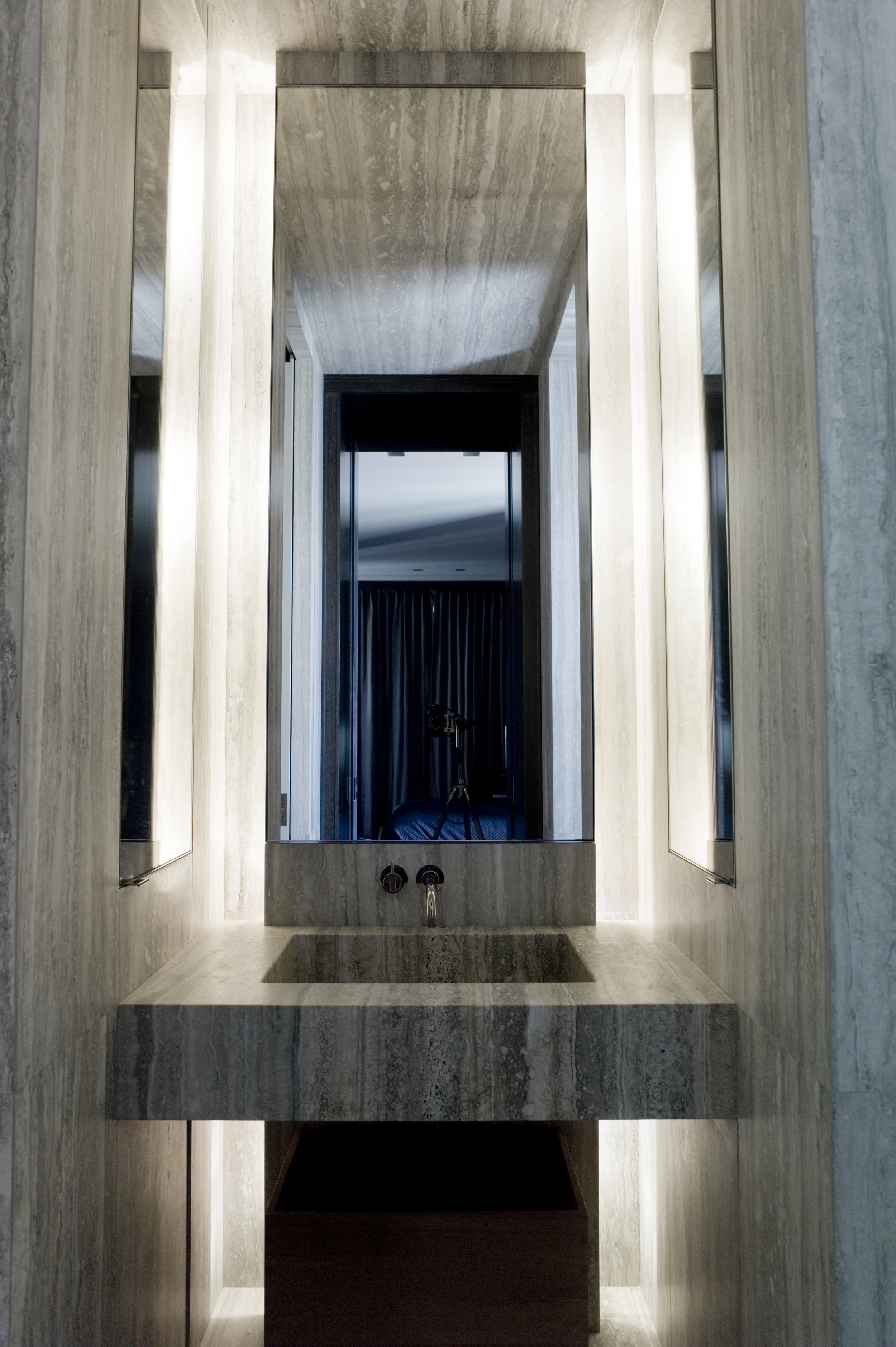 Vanity carved from silver travertine in guest bathroom