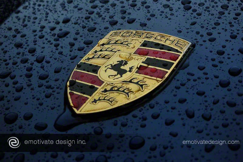 The cliché shot of the Porsche crest covered in and surrounded by water droplets.