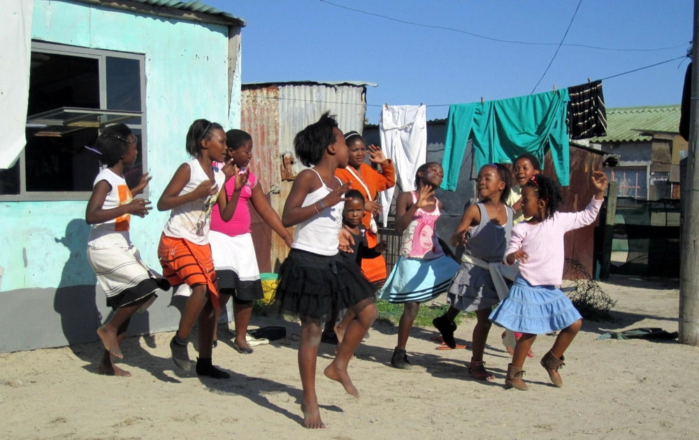 Girls in Khayelitsha, South Africa, dance at an open air campaign for an HIV support group