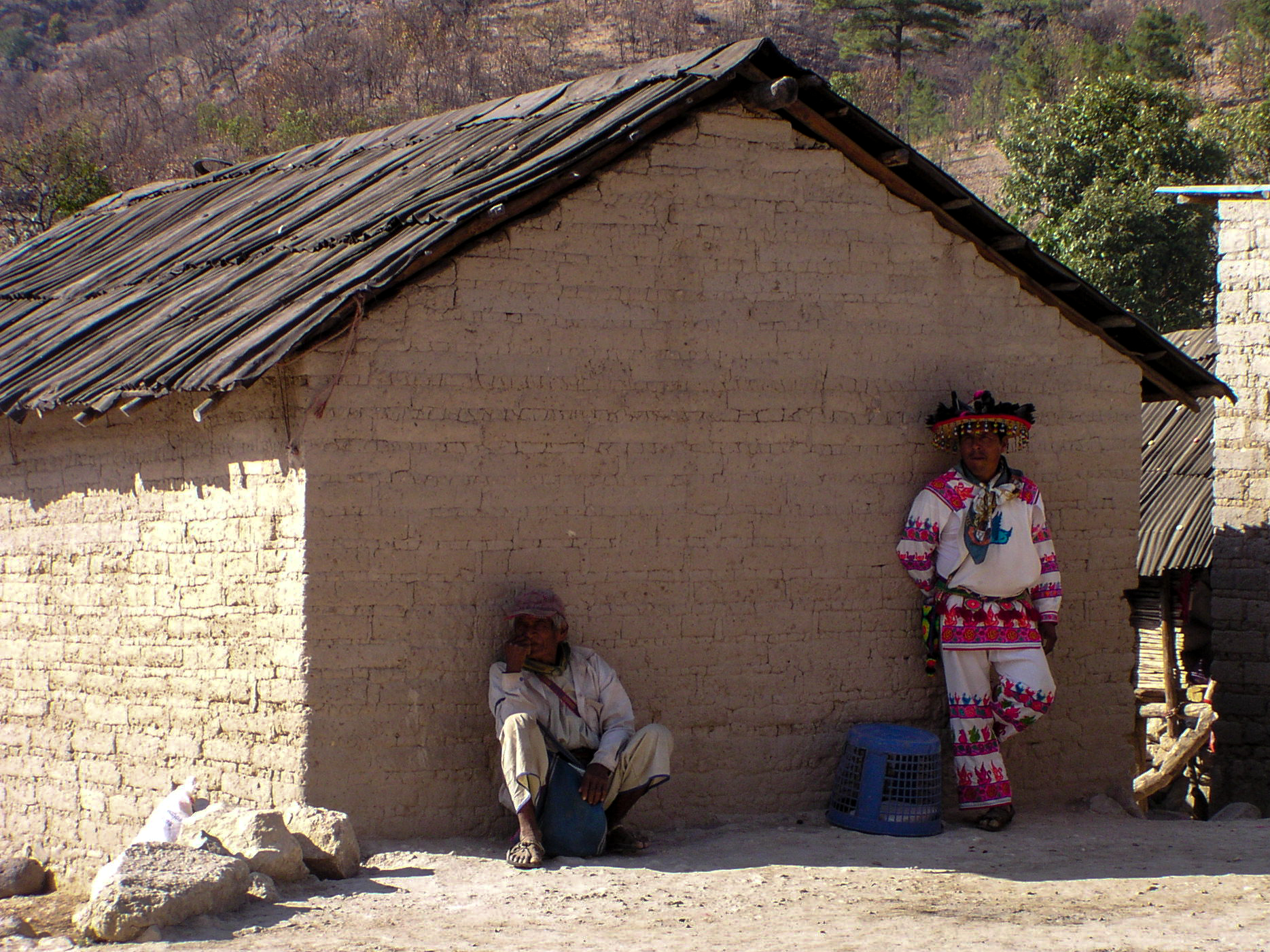 Wixarica man in traditional costumes observe us from the distance