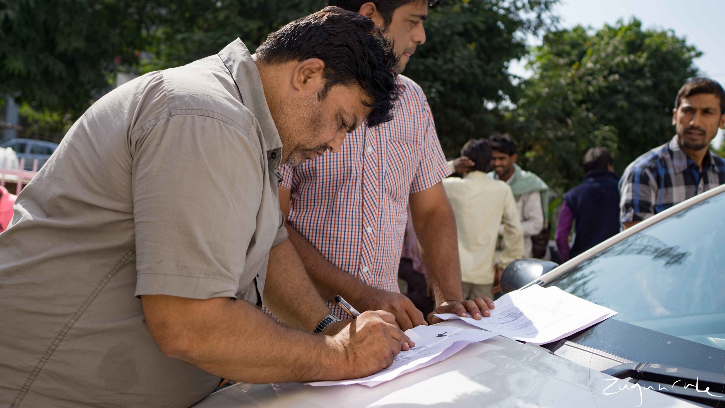 A man fills out exchange paperwork on the hood of a car (Jaipur)