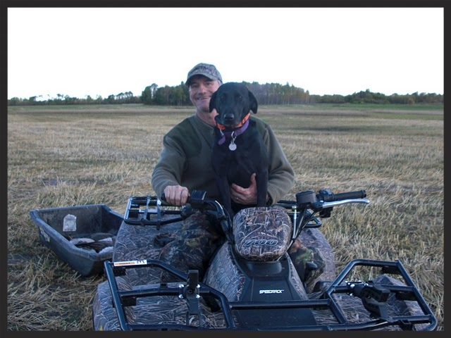 Jim and Kole ride an ATV on one of their many great pheasant hunts