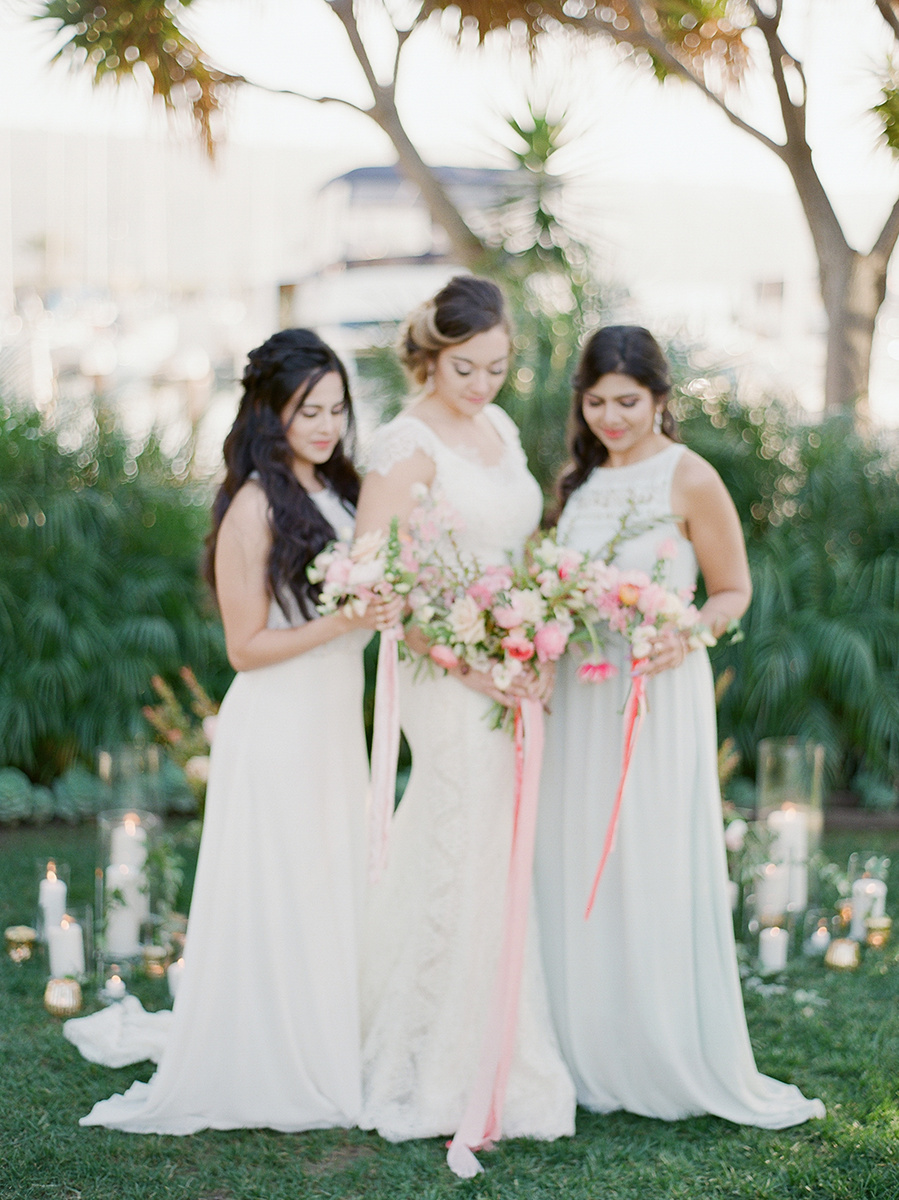 Bride and bridesmaids wedding dress and hairstyle inspiration with pretty pink bouquet with silk velvet ribbons