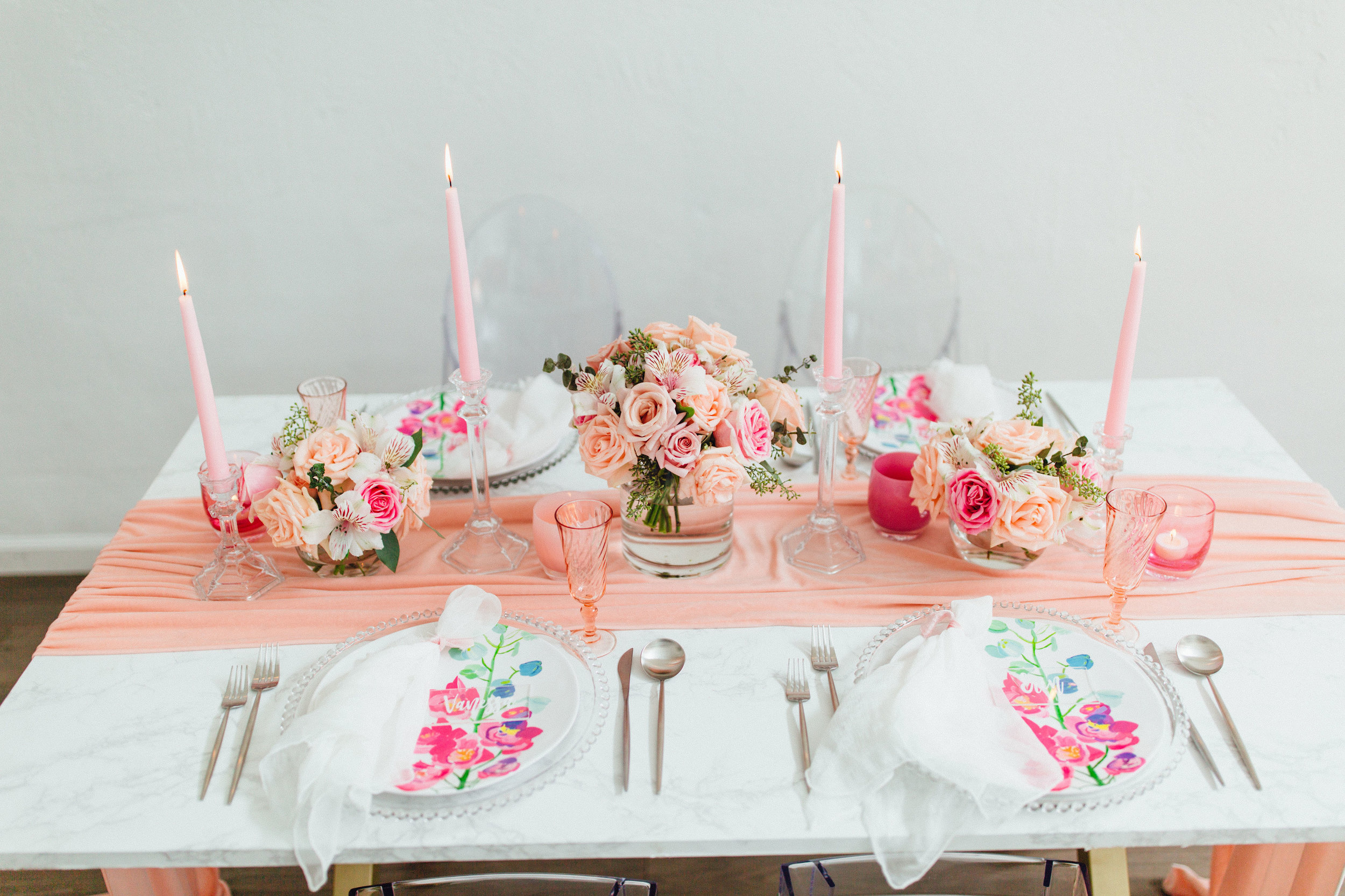 Pretty coral and peach tablescape for galentines with floral arrangements and silk table runners