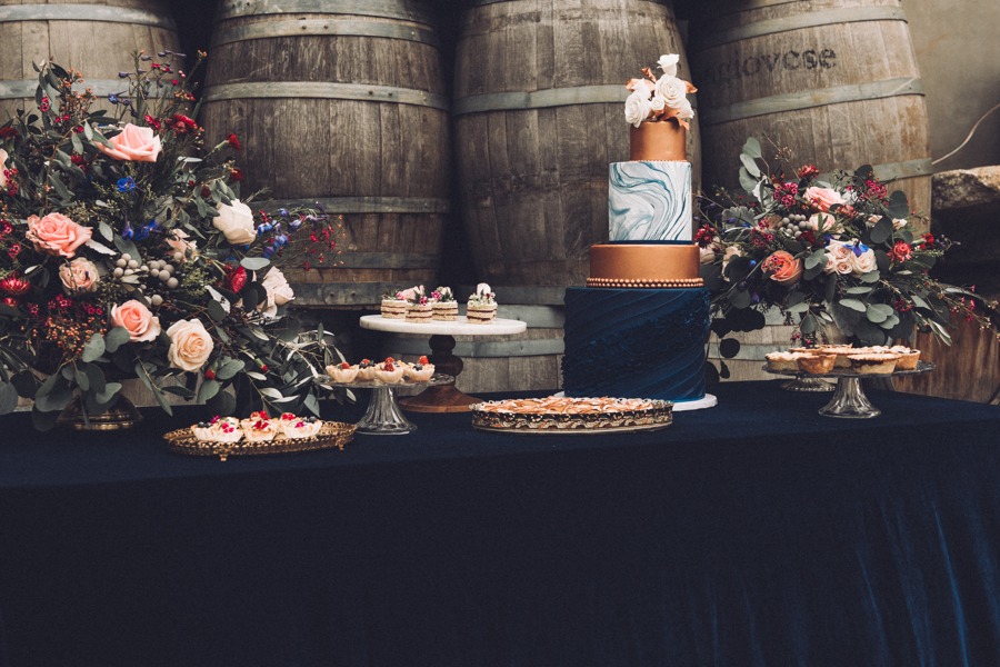 Elegant wedding cake and dessert table using dark blue velvet linens