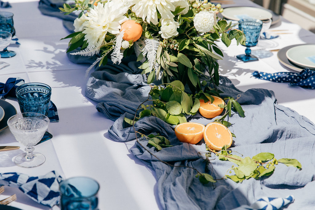 Gauze table runners partnered with blue table napkins and tableware for wedding tablescape