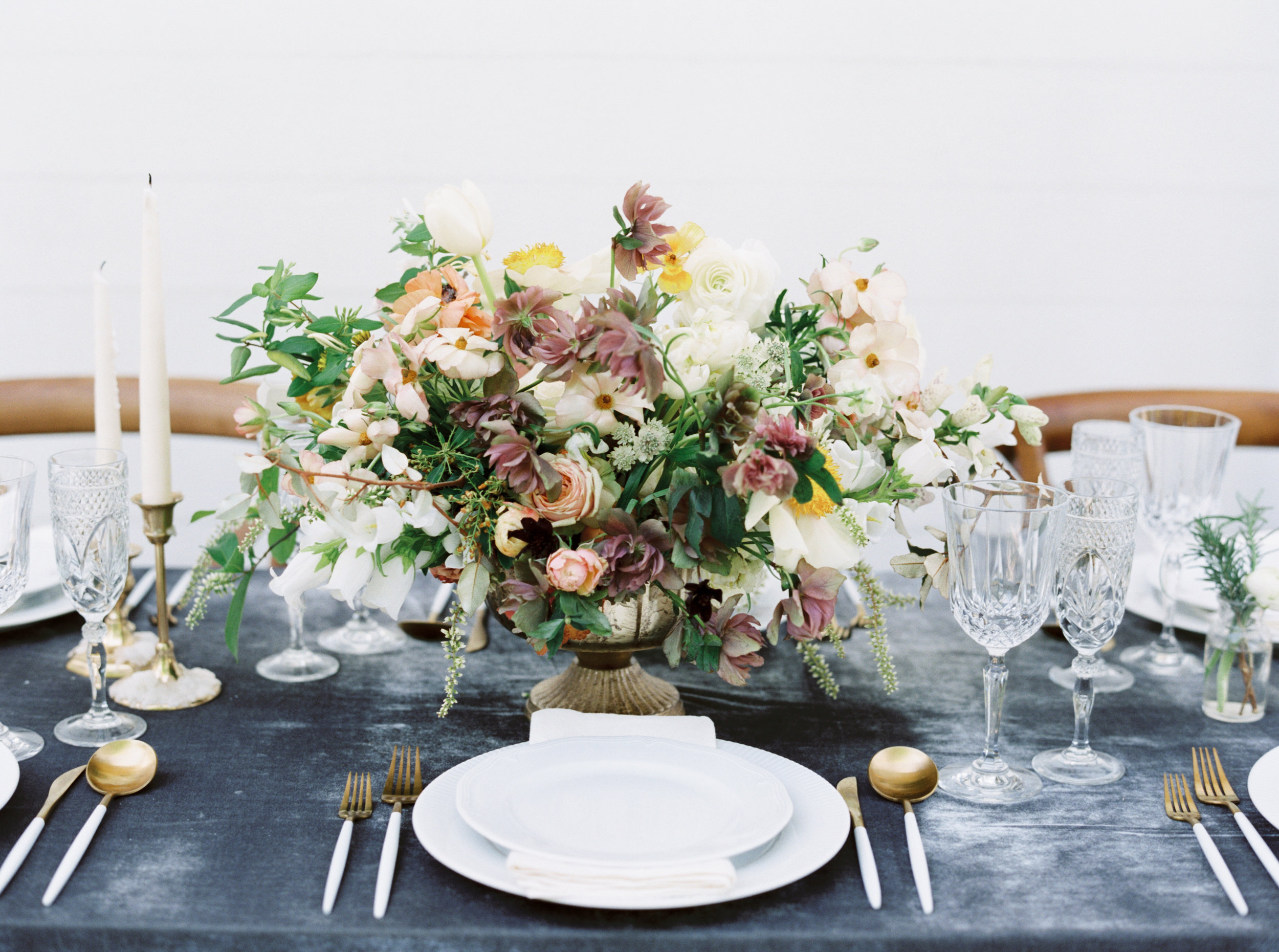 elegant wedding reception tablescape using gray silk velvet table linen and gold and white tableware
