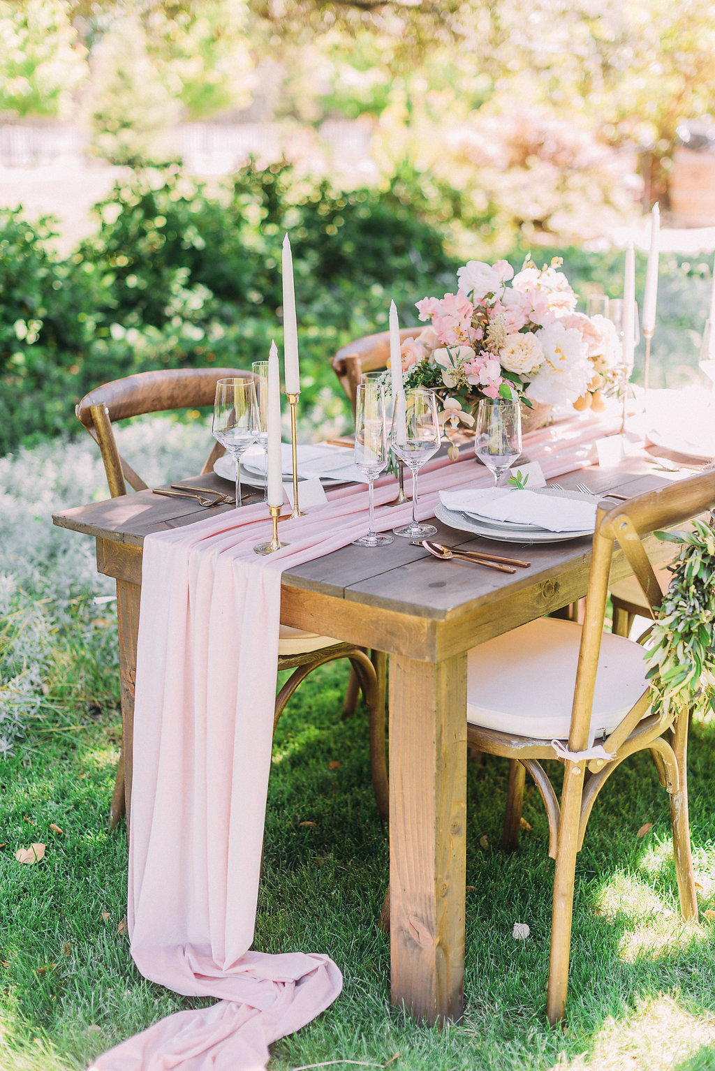 Flowy Pink Silk Chiffon Table runners and Pink Floral arrangements on wooden table for outdoor wedding venue