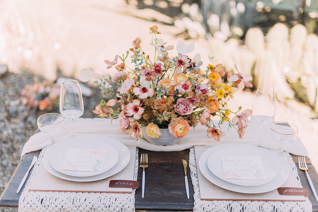 Pretty Spring florals wedding tablescape using white silk chiffon table runners and patterned table linens