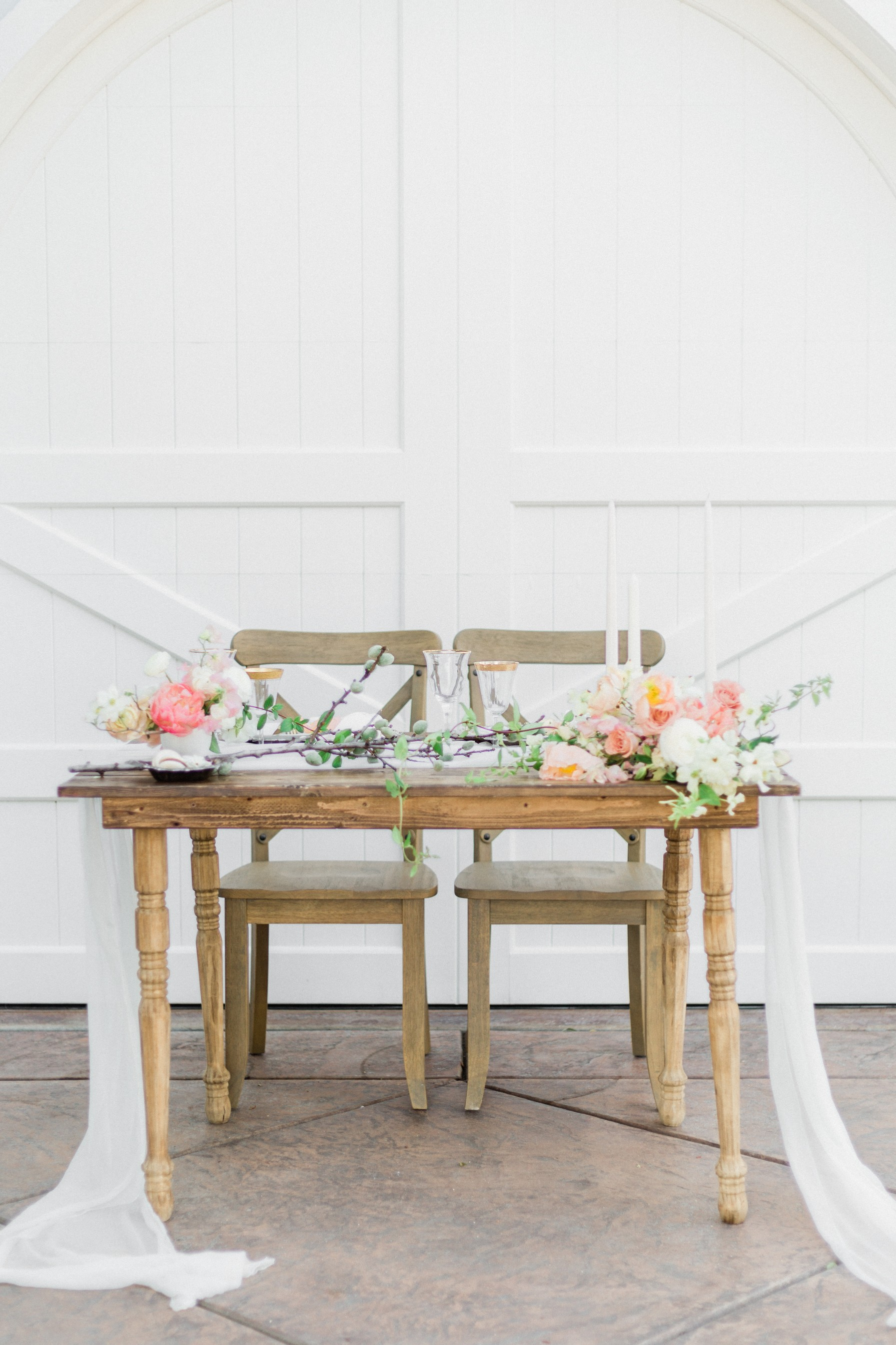 Simple wooden table designed with silk chiffon table runners and floral arrangements for spring wedding inspiration tablescape