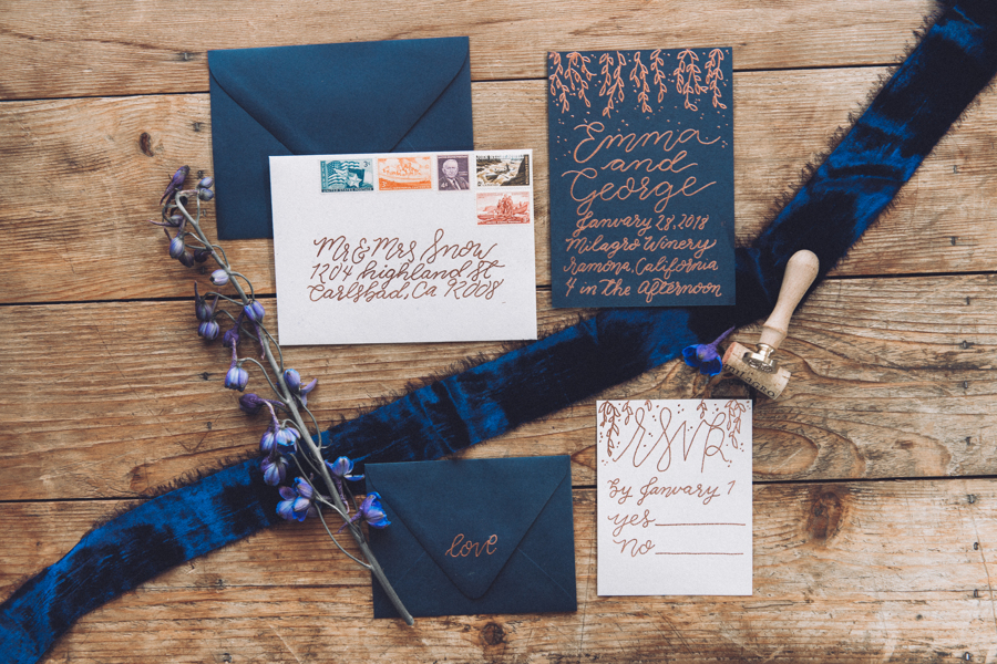 Dark blue themed wedding invitation with calligraphy and silk velvet ribbon flat lay