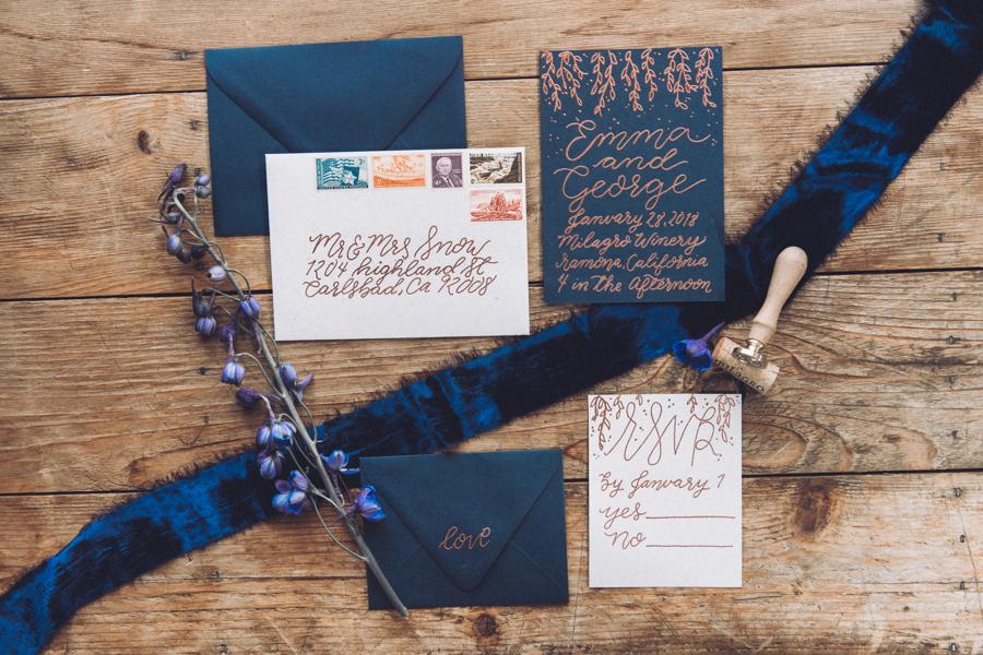 Dark blue themed wedding invitation with calligraphy and silk velvet ribbon flat lay