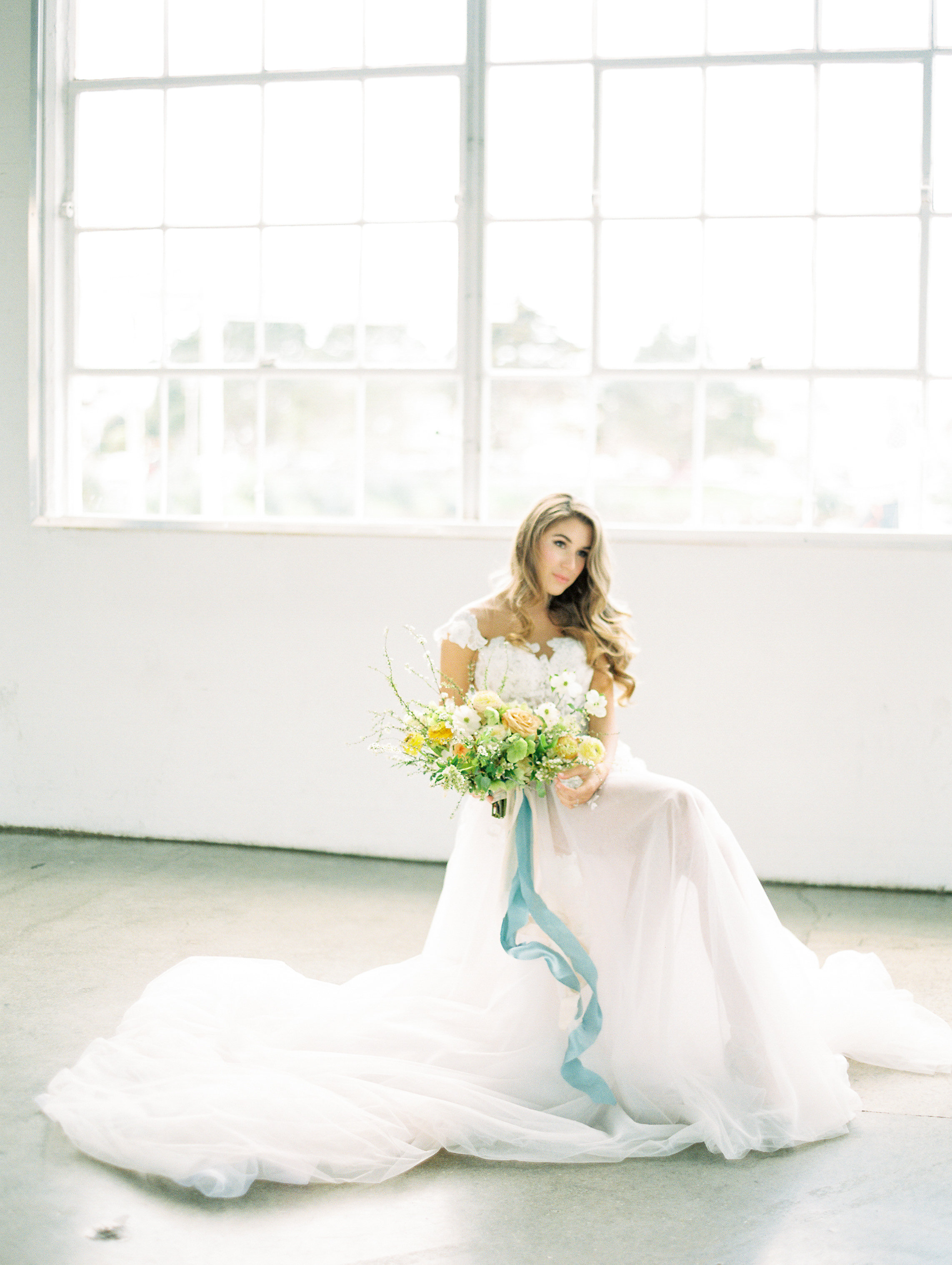 Beautiful and dreamy white wedding gown with fresh and lively bridal bouquet designed with long and flowy blue silk ribbons