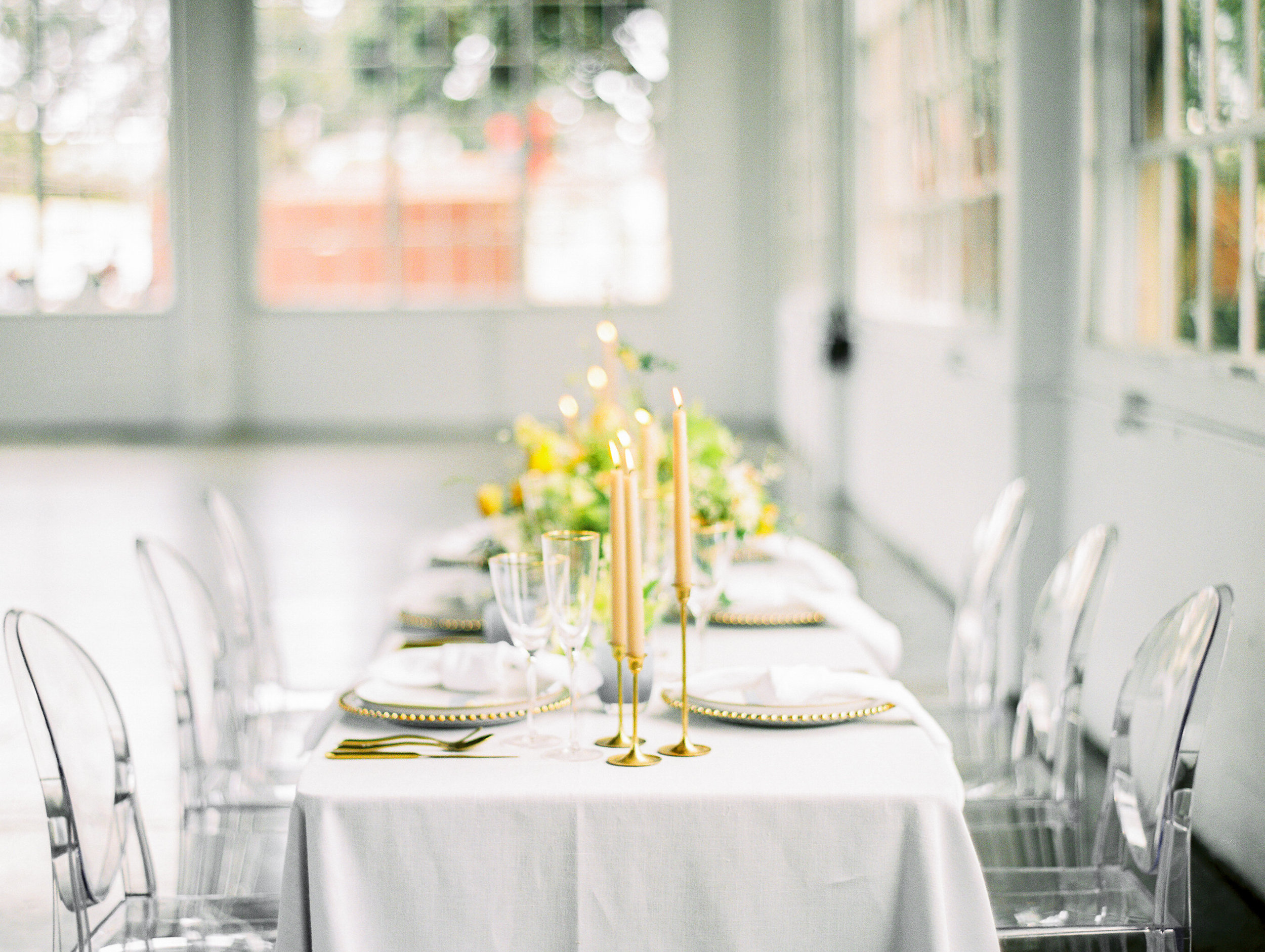 Simple White, Gold, and Green Wedding Tablescape With Transparent Chairs