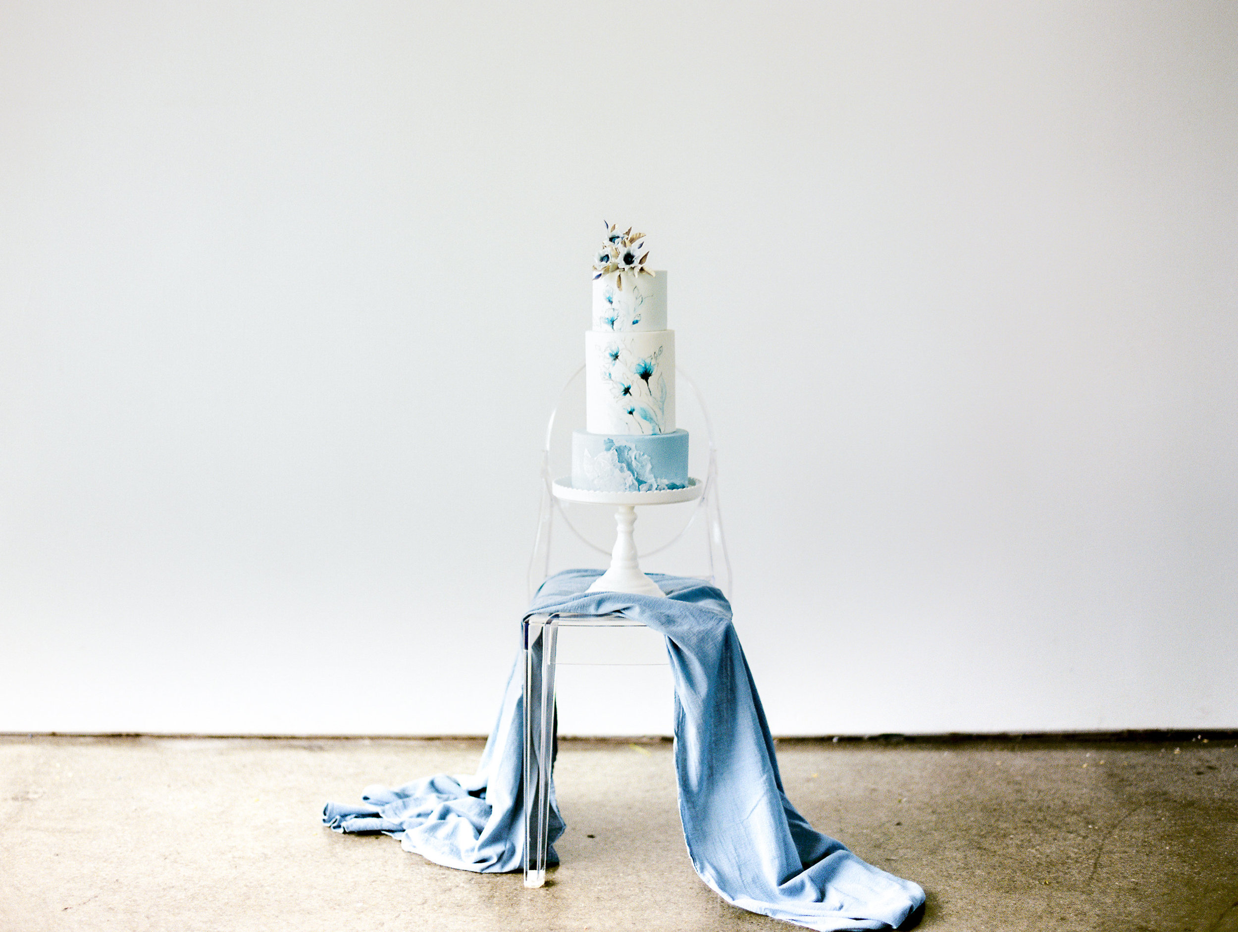 Simple blue wedding cake with white cake stand and powder blue table runners